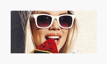 Blonde girl in white sunglasses eating watermelon popsicle