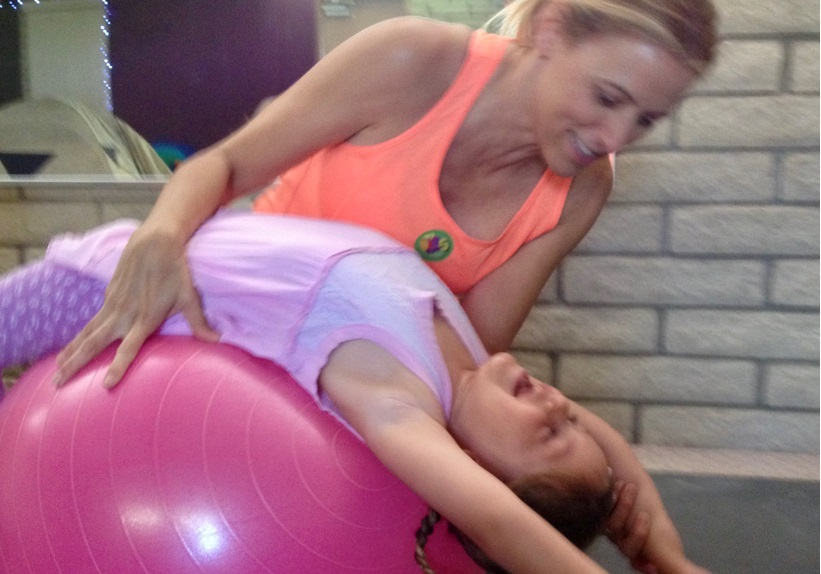 therapist working with child on ball moves