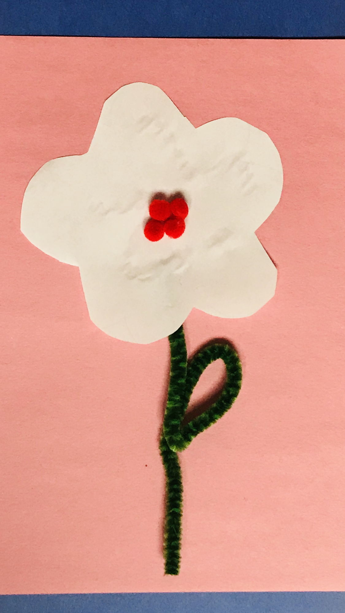 White paper flower with green pipe cleaner stem on pink paper