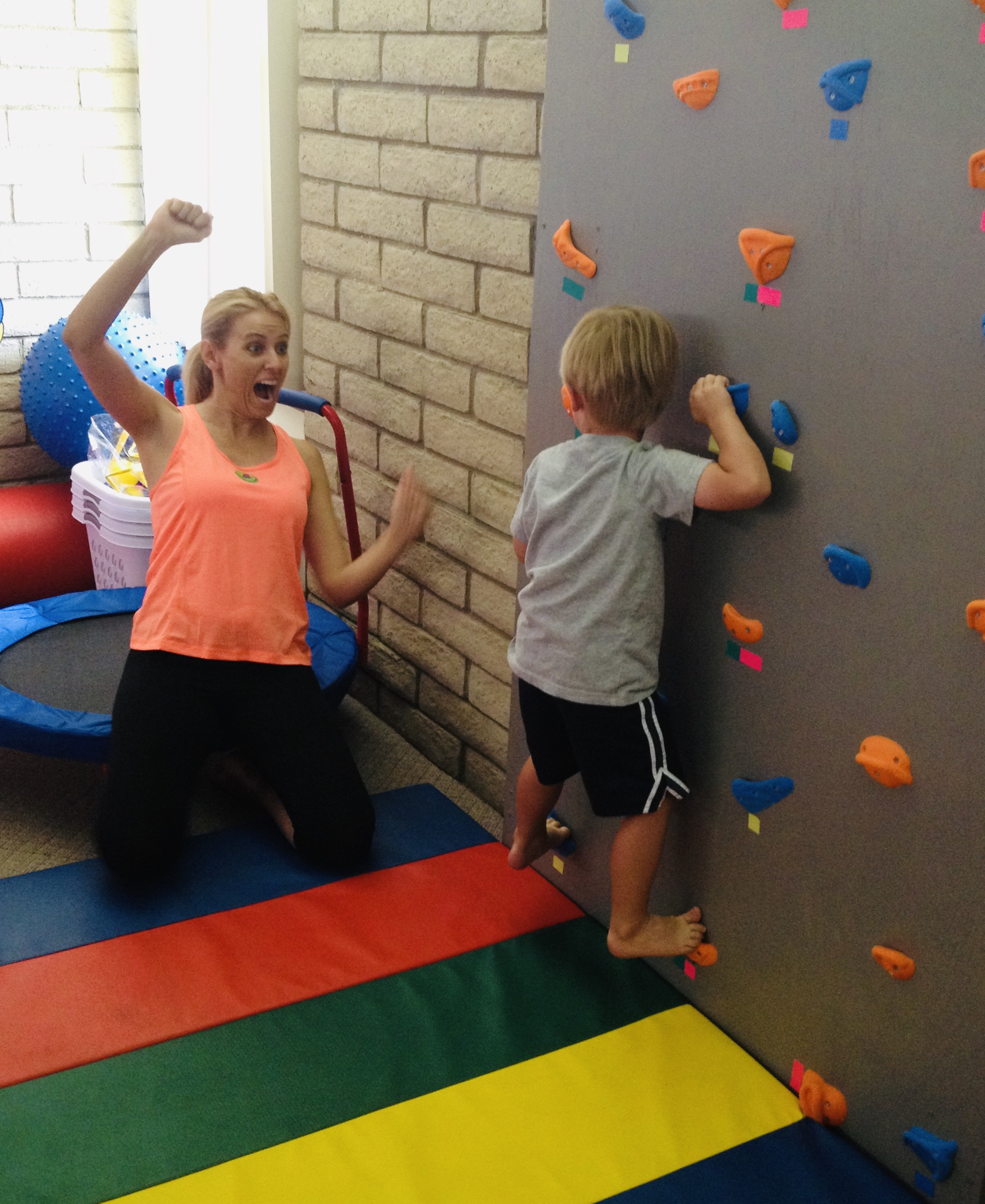 Woman encouraging little boy on rock climbing wall