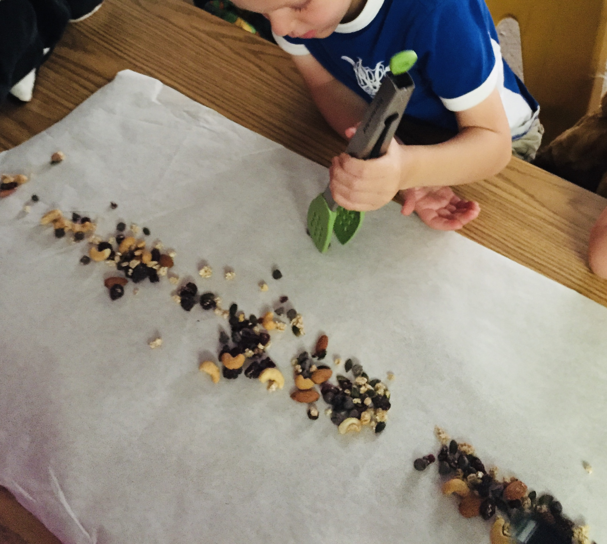 Kid holding tongs with line of assorted nuts