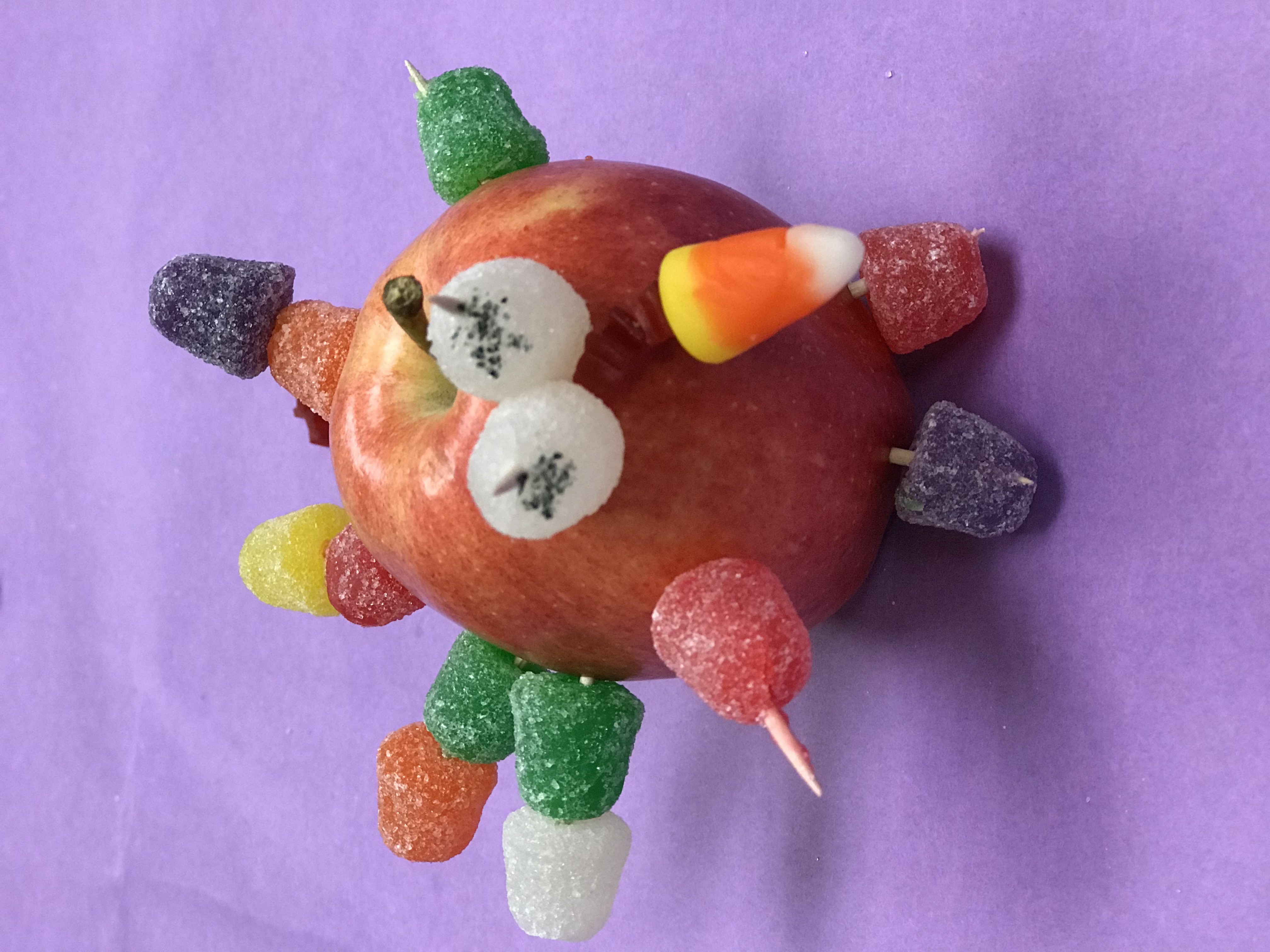 Apple covered with sugar candies on toothpicks