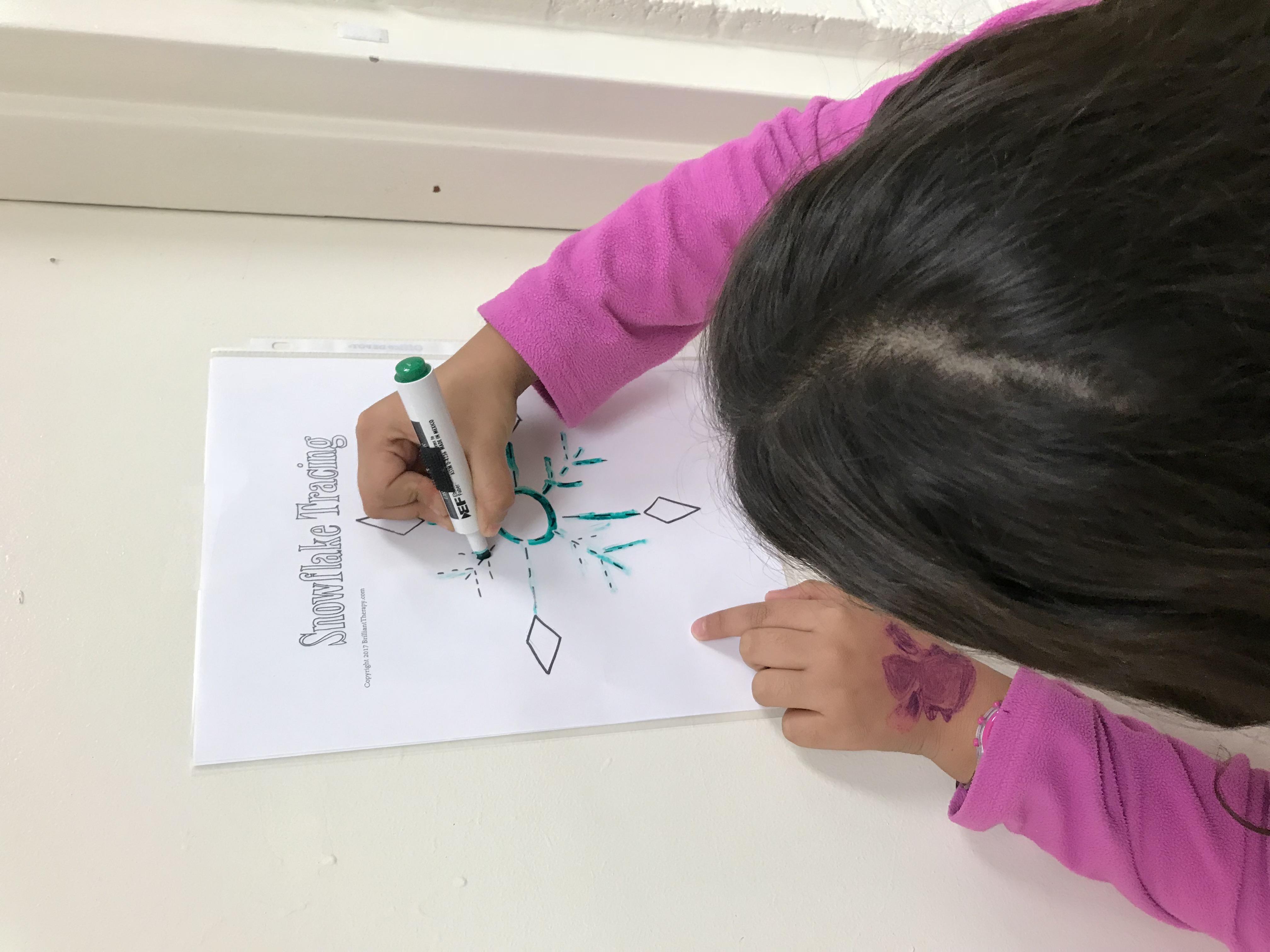Kid drawing snowflake on template