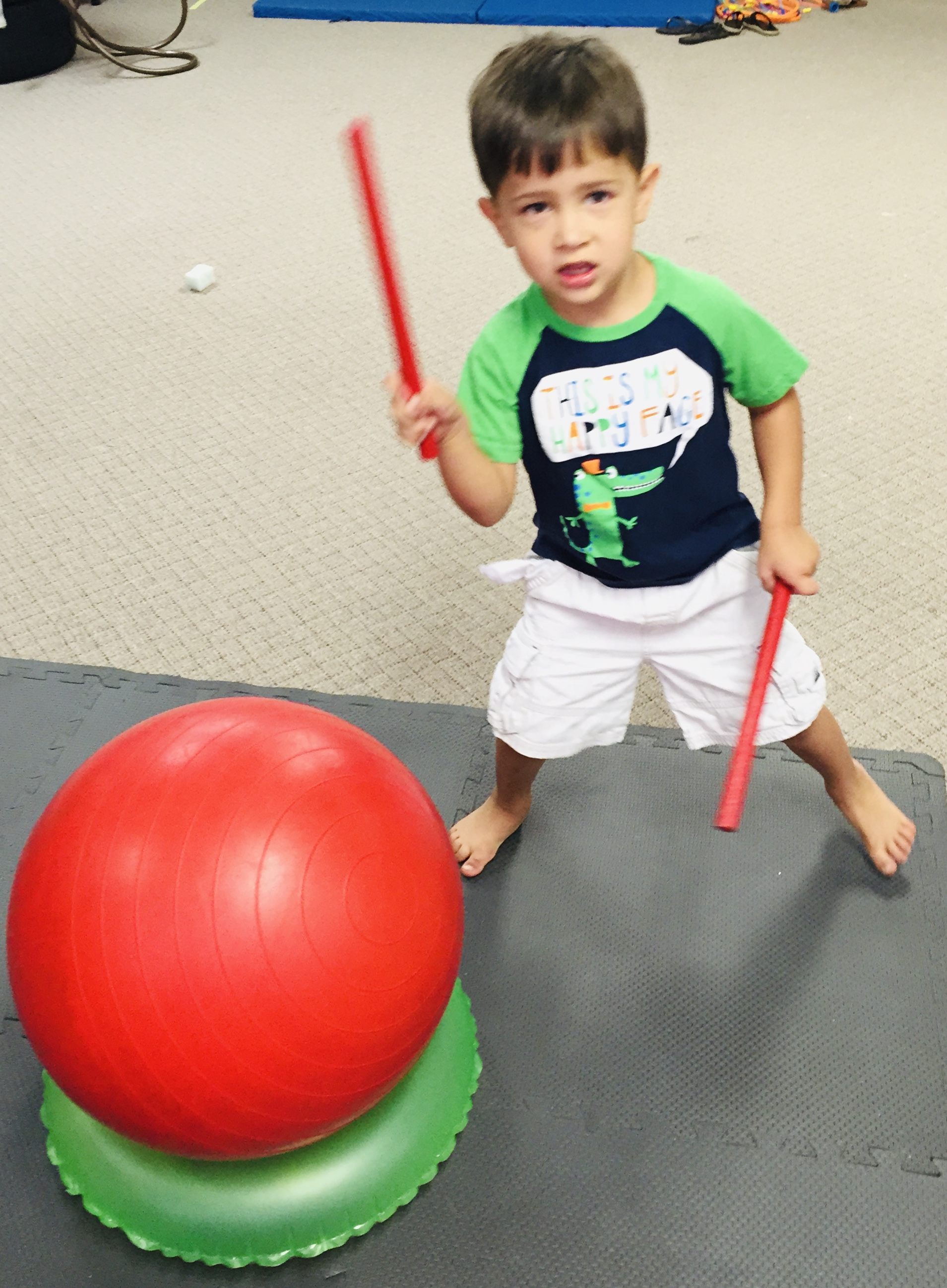 Boy hitting yoga ball with drumsticks