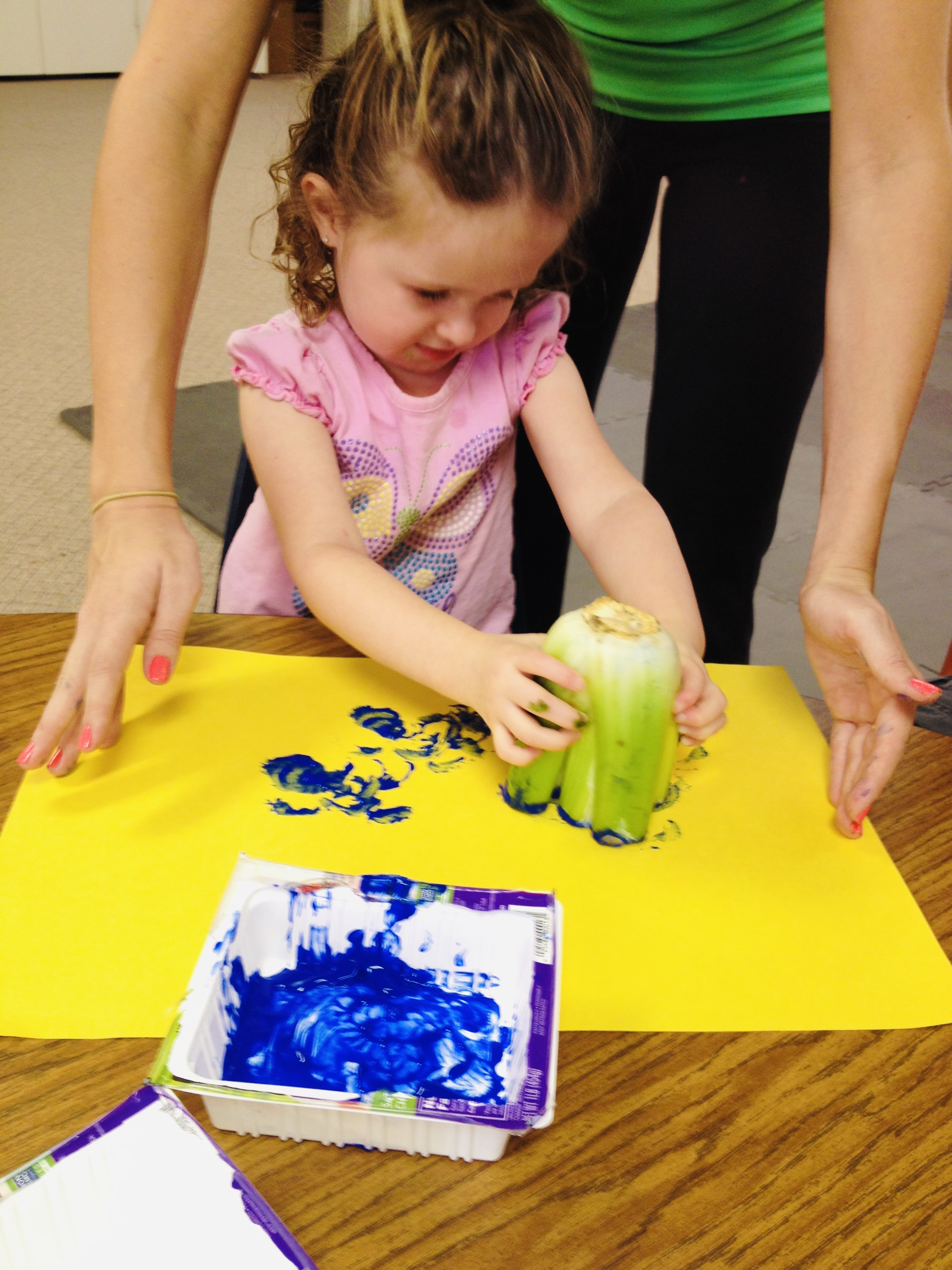 Little girl paint stamping with celery