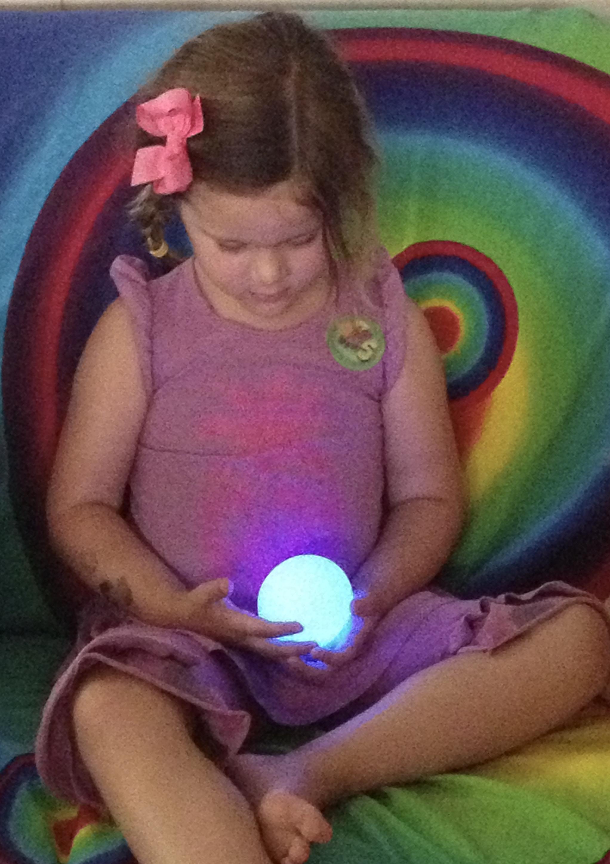 Little girl holding blue glowing magic egg