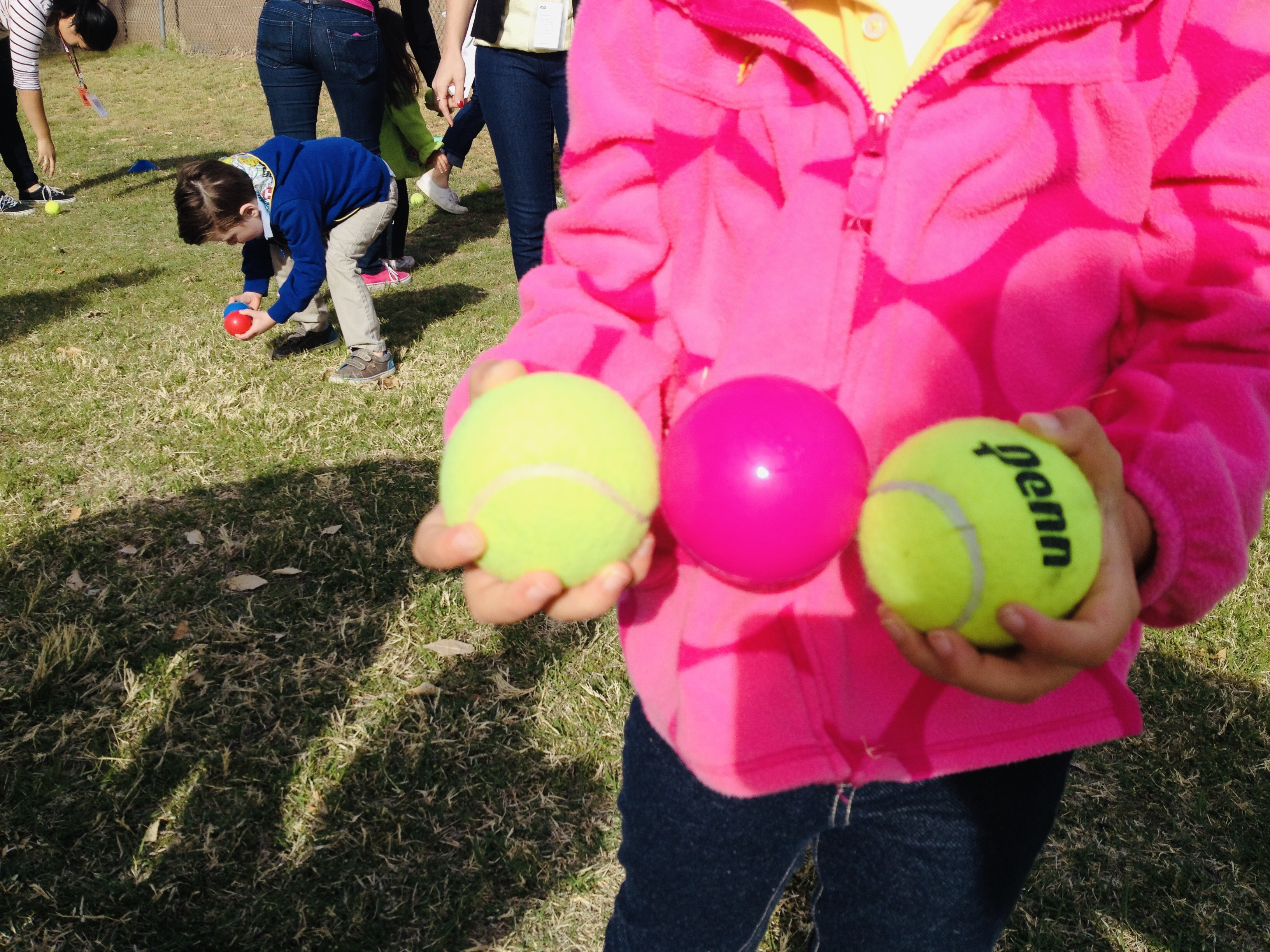 Little girl holding two tennis balls to balance a pink plastic ball in between