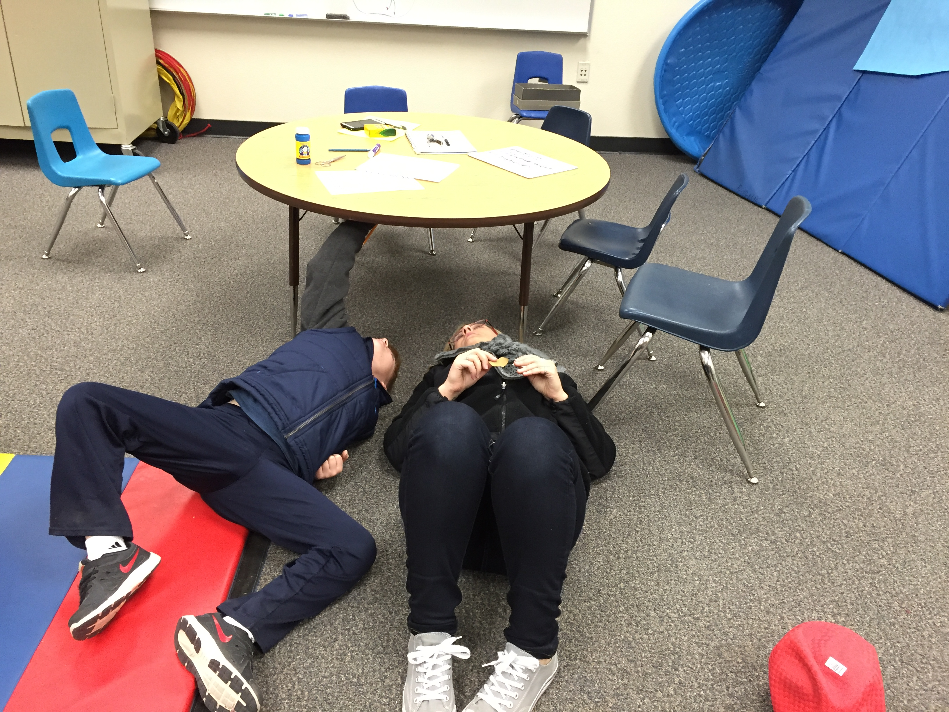 Two people laying on floor looking under table