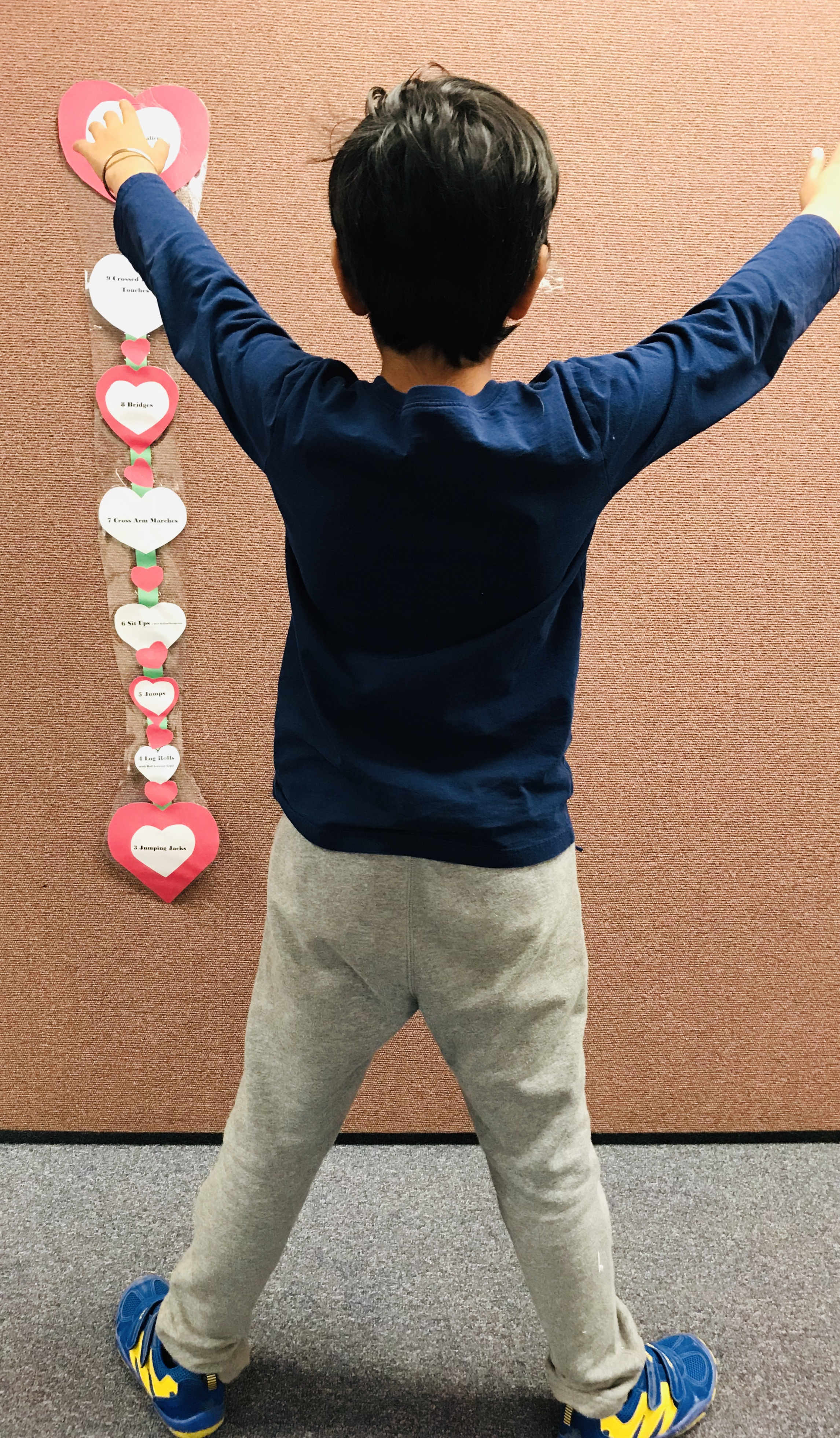 Kid standing and stretching to Heart papers