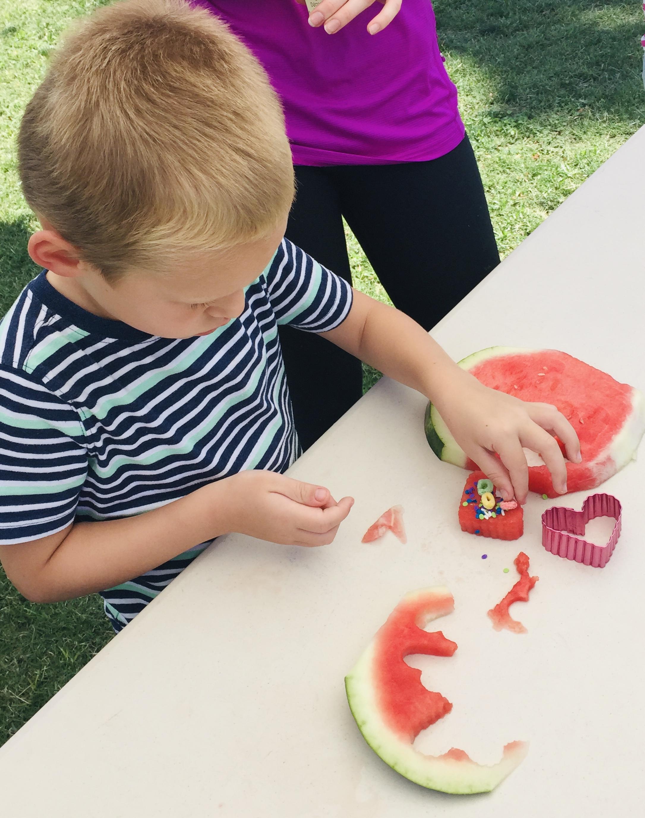 Kid placing Fruit Loops on watermelon heart