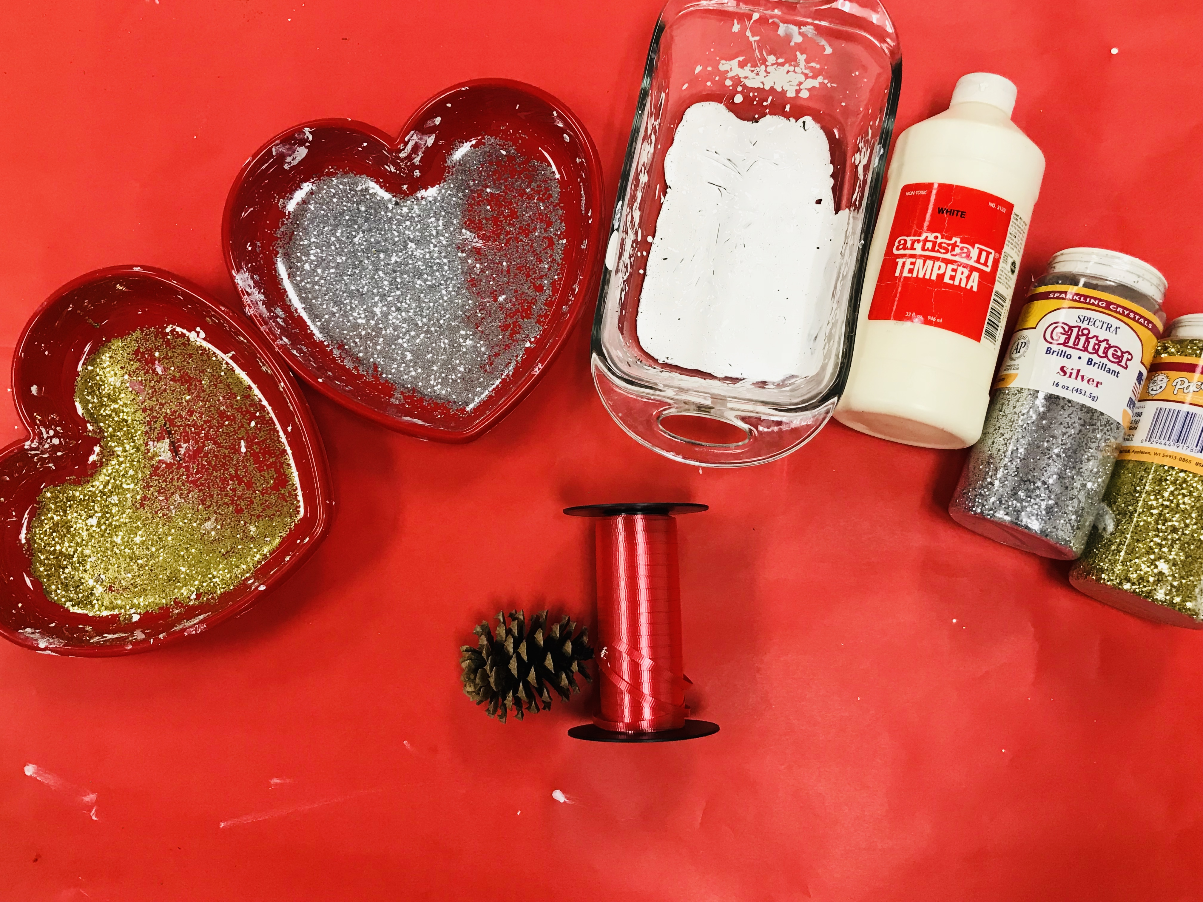 Red ribbon and bowls of glitter and glue