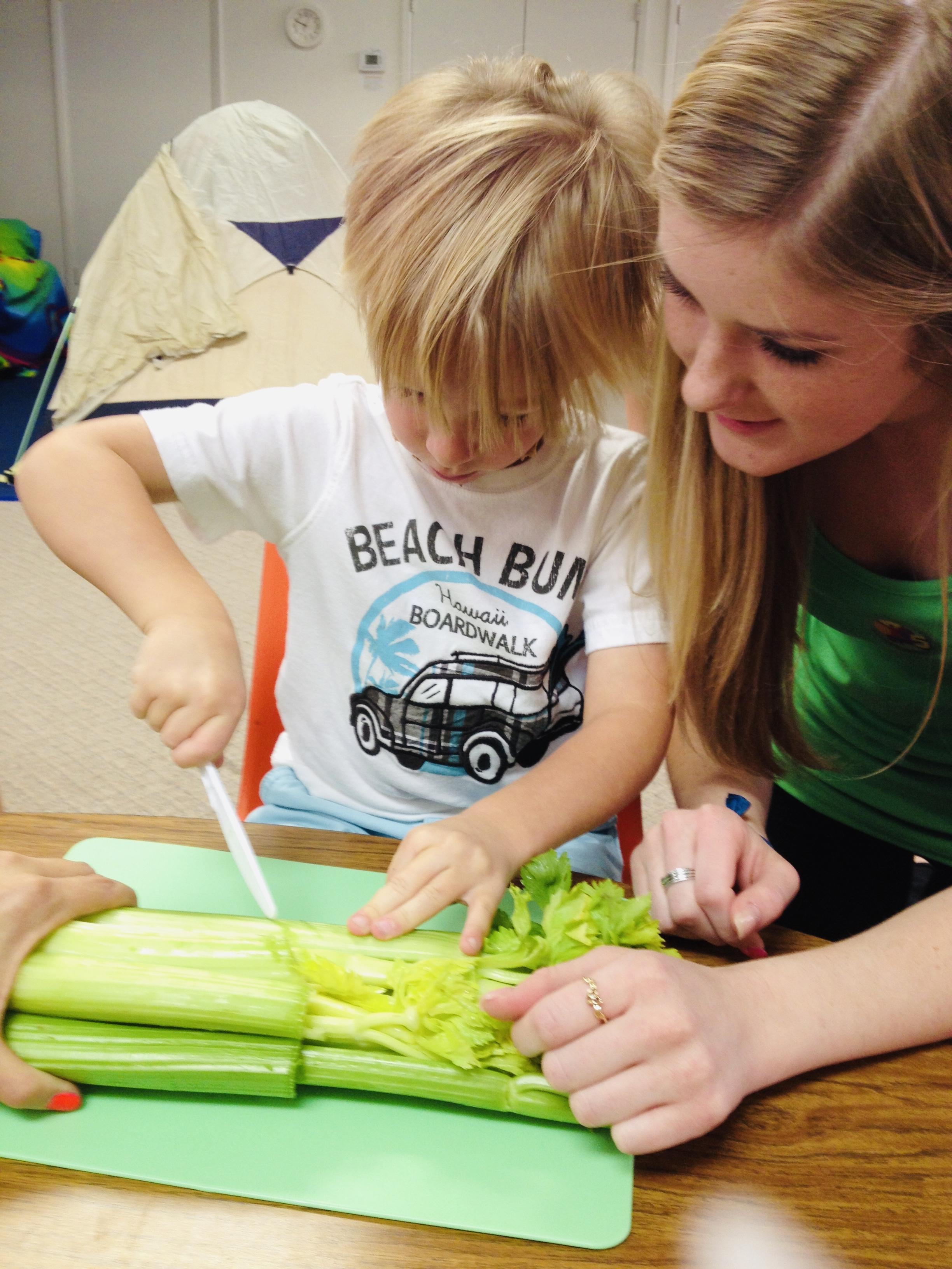 Woman helping little boy cut celery