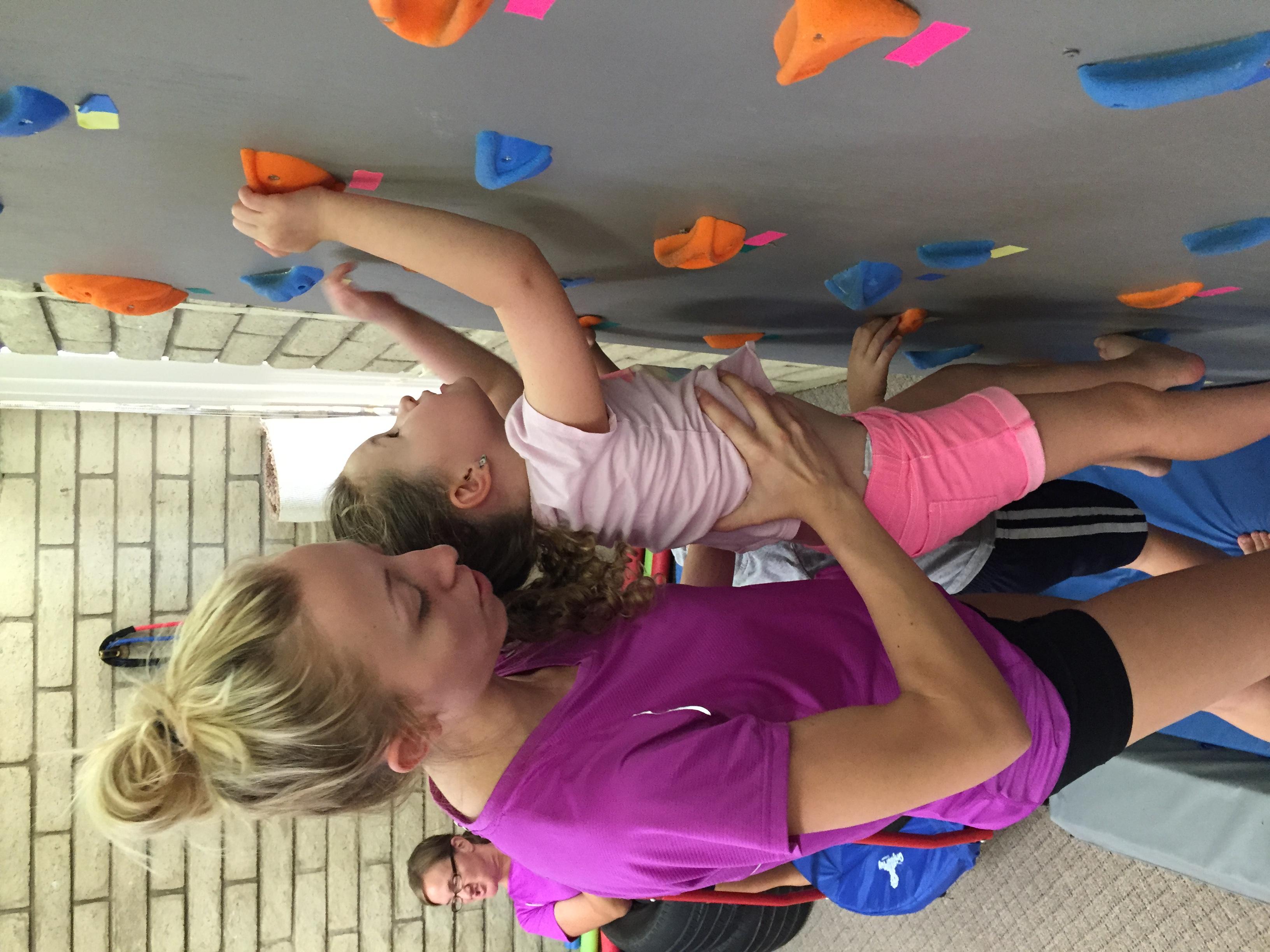 Woman assisting little girl up rock climbing wall