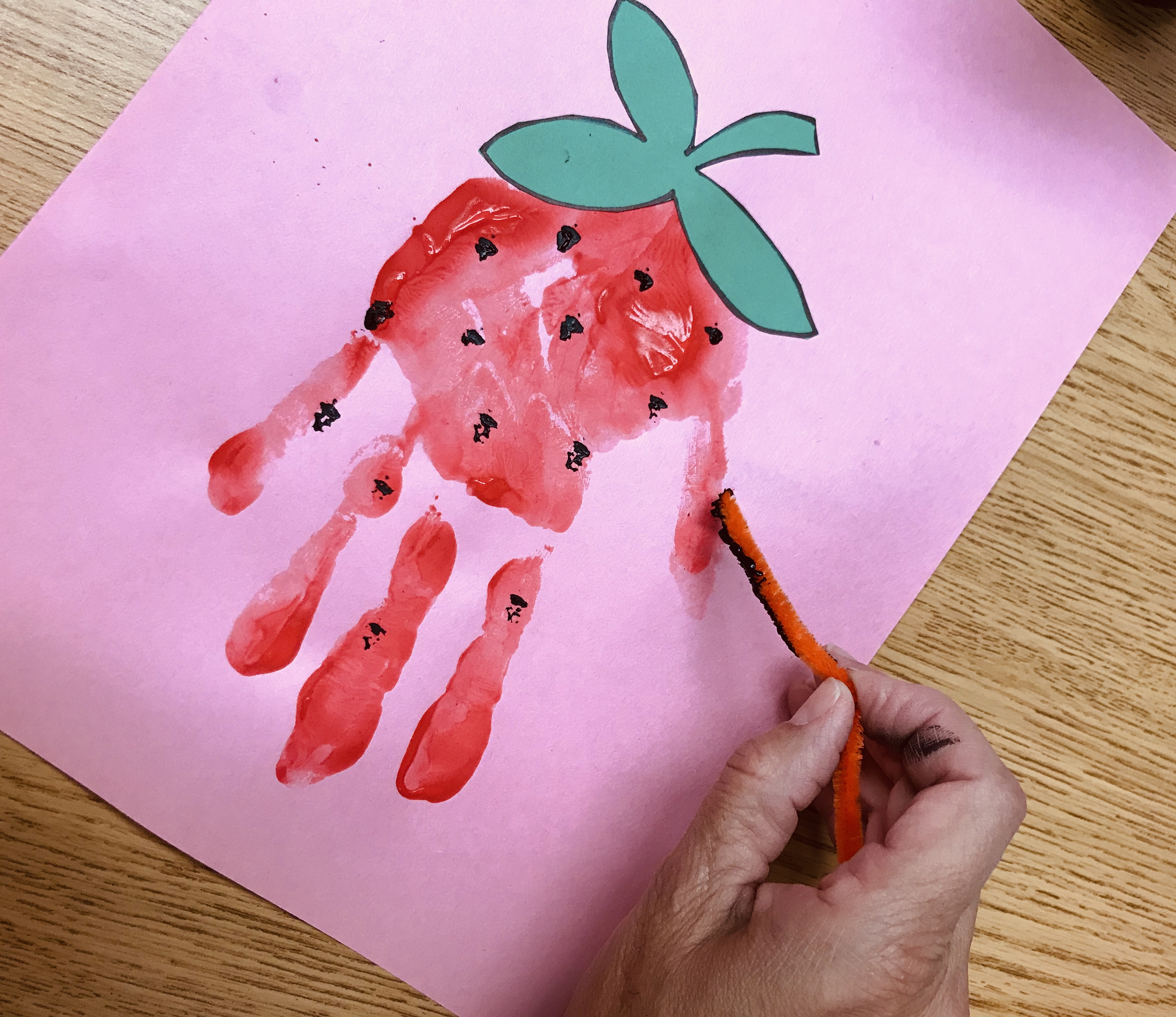 Using pipe cleaner stem to paint strawberry