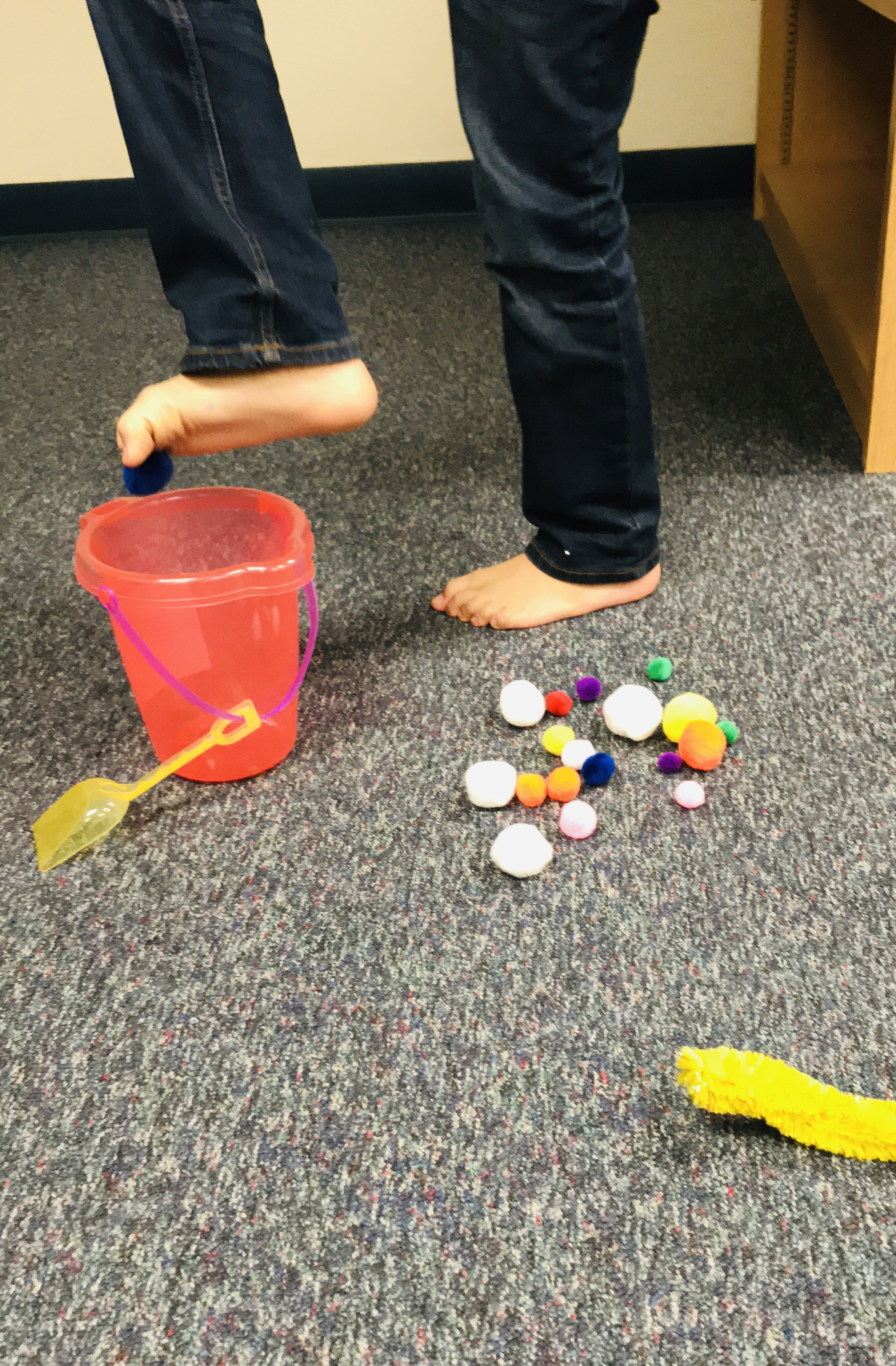 Using bare feet to pick up fuzzy balls to put in bucket