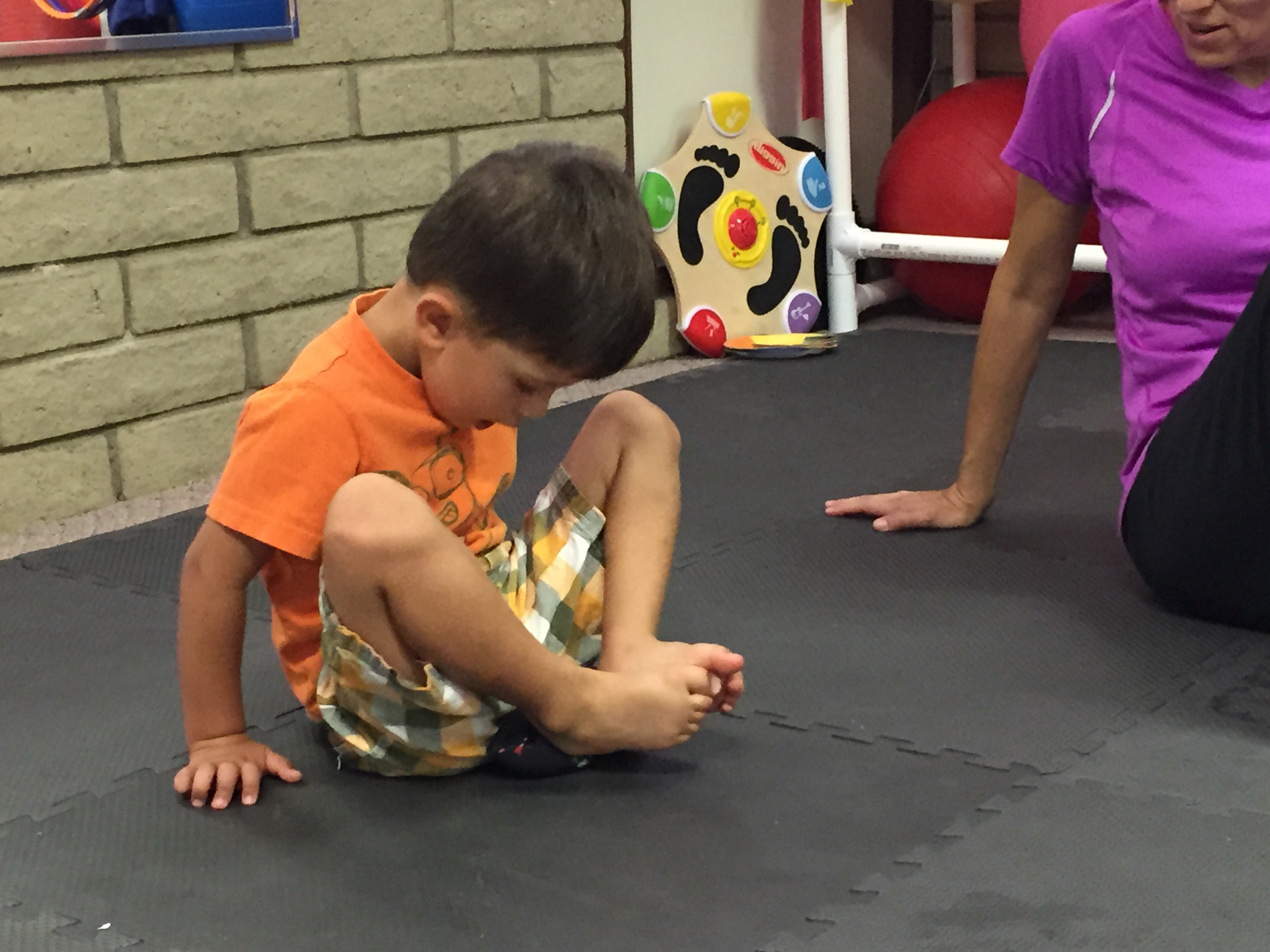 Kid picking up item with feet