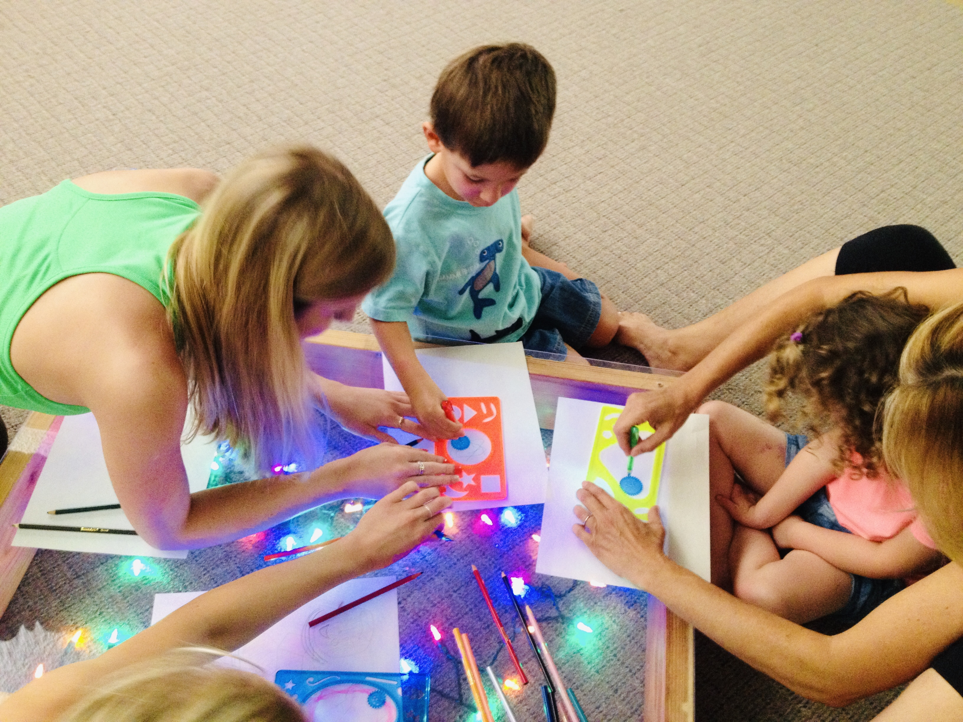 Kids and adults playing on makeshift light table