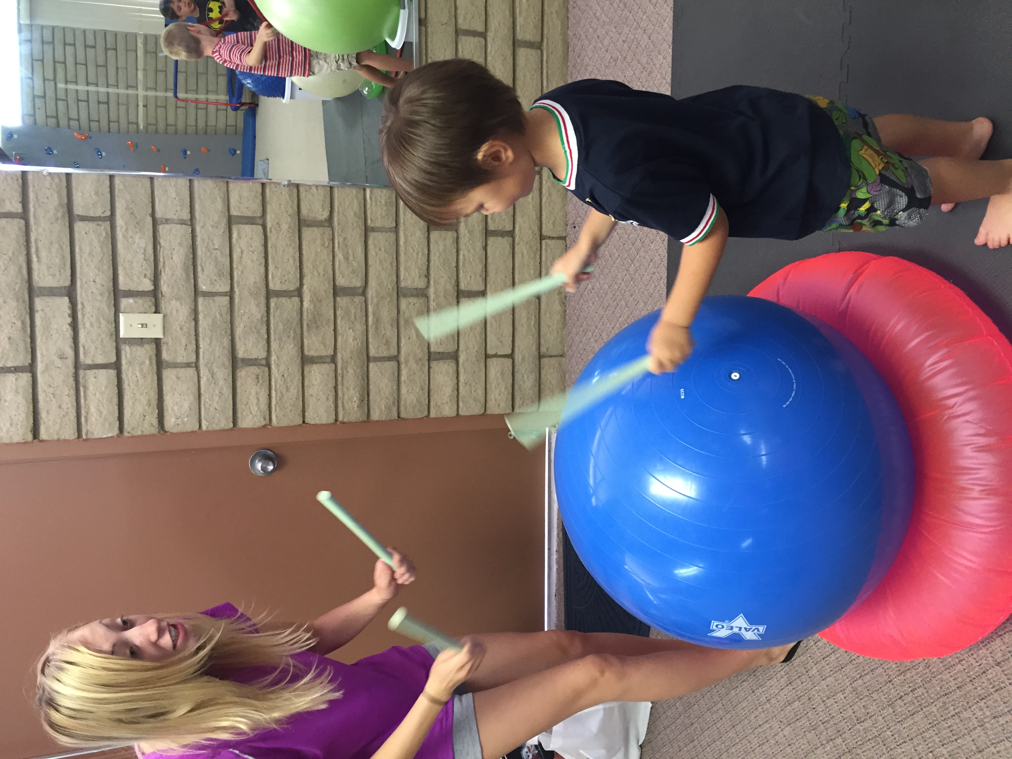 Woman and little boy playing with drumsticks on yoga ball
