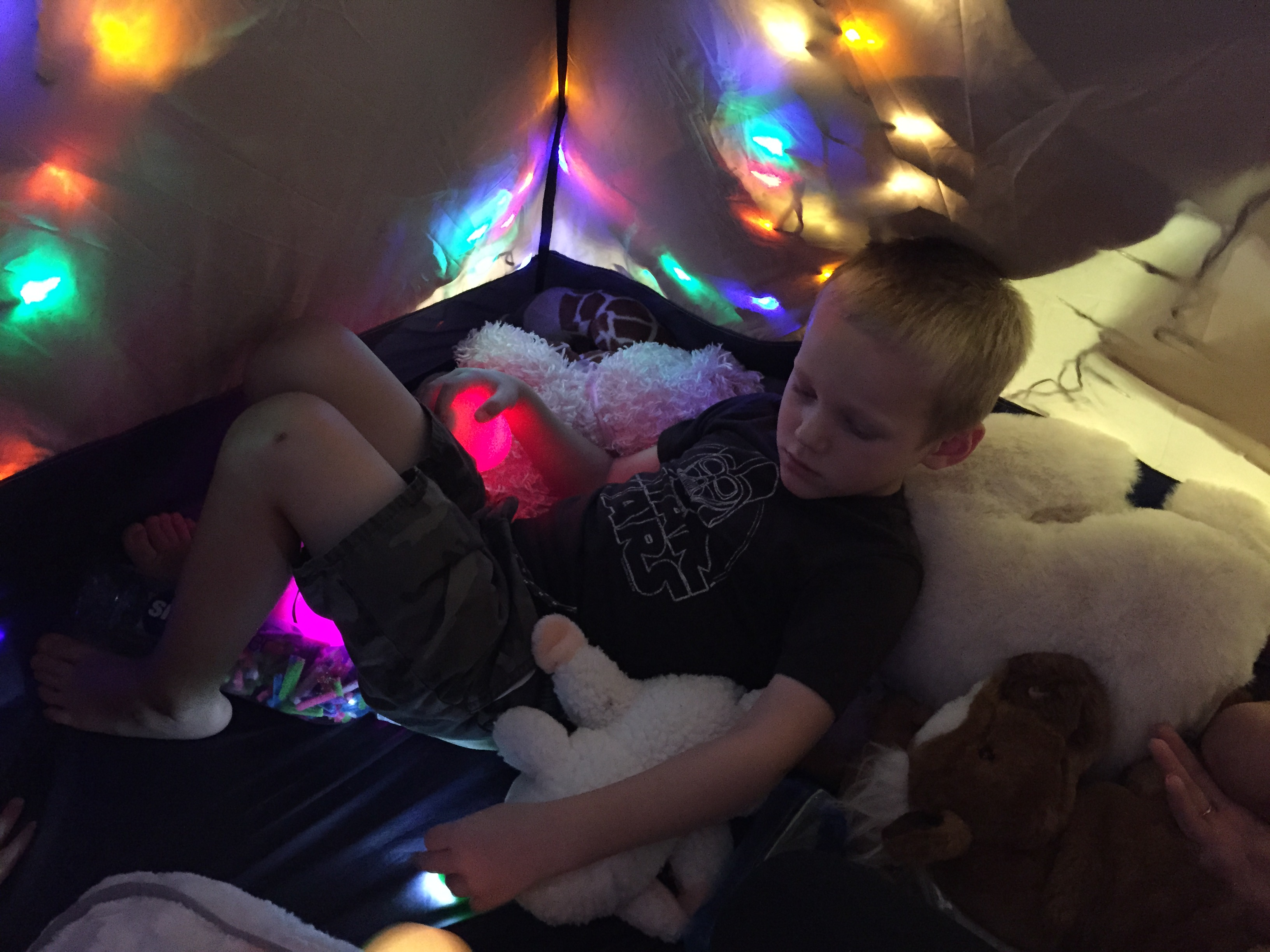 Little boy in blanket fort with a pink glowing magic egg