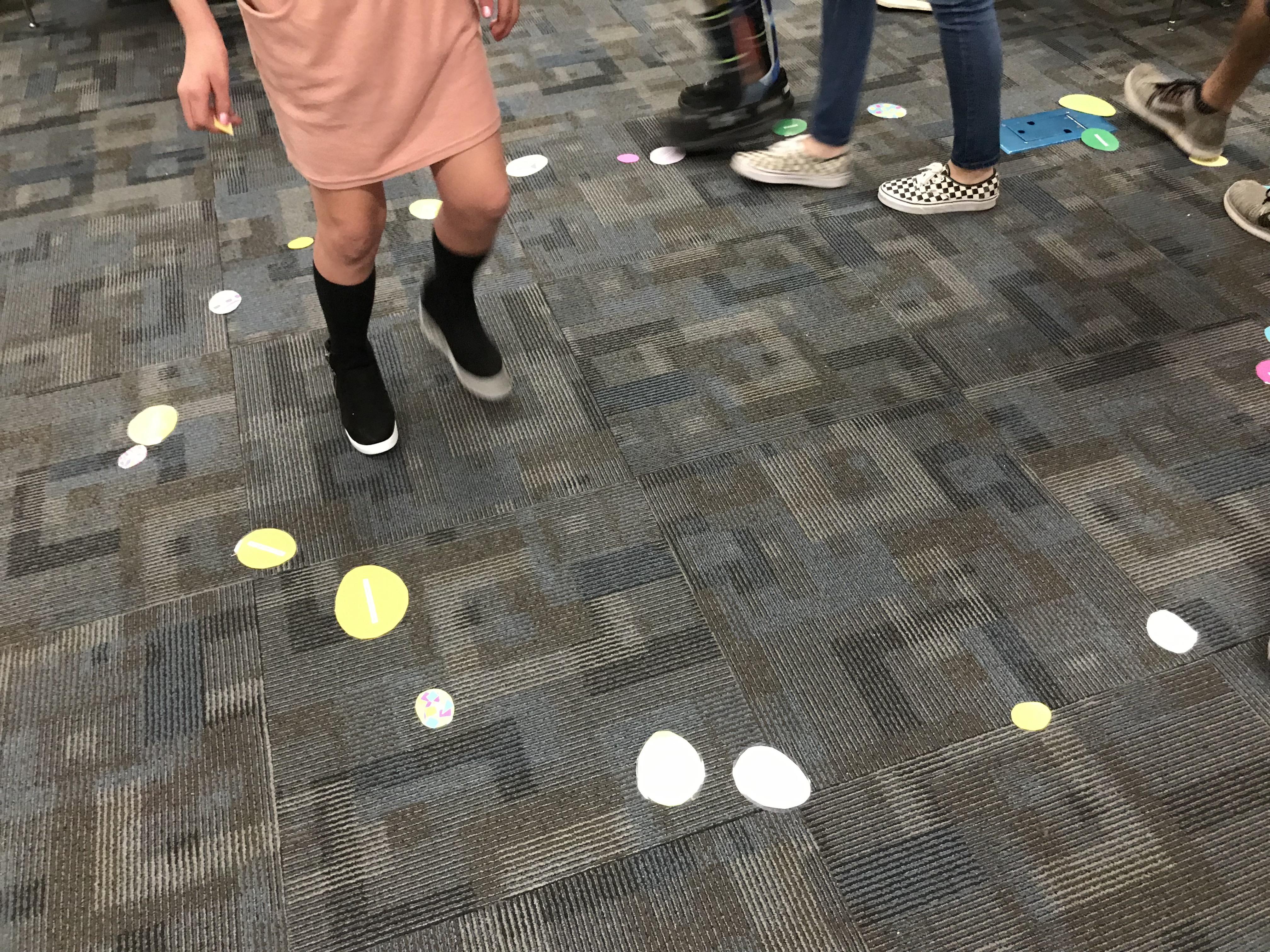 Kids playing around paper circles on carpet