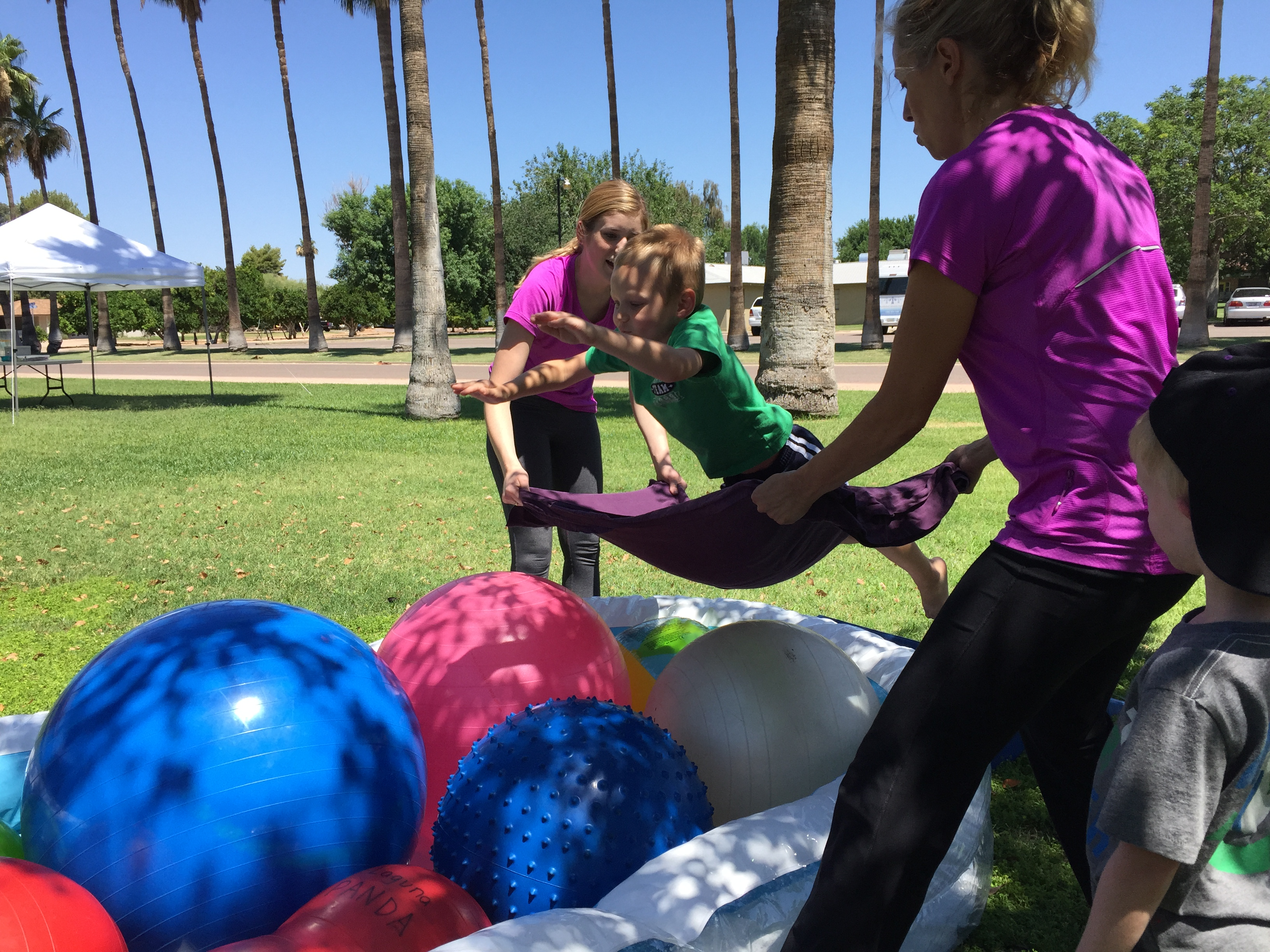 Kid jumping onto blanket that two women are holding over yoga balls