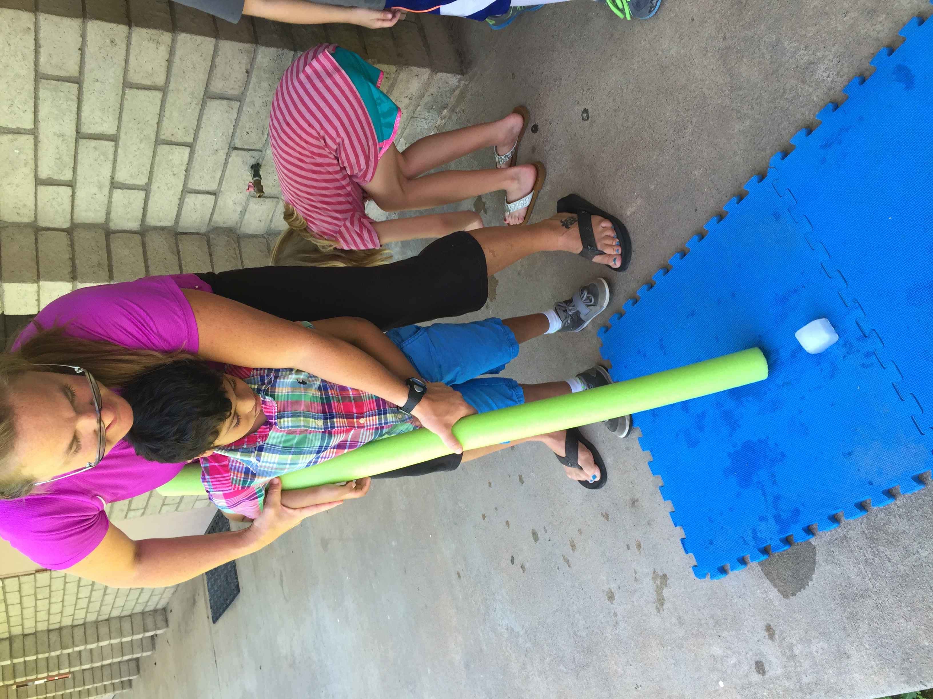Woman helping little boy golf with pool noodle