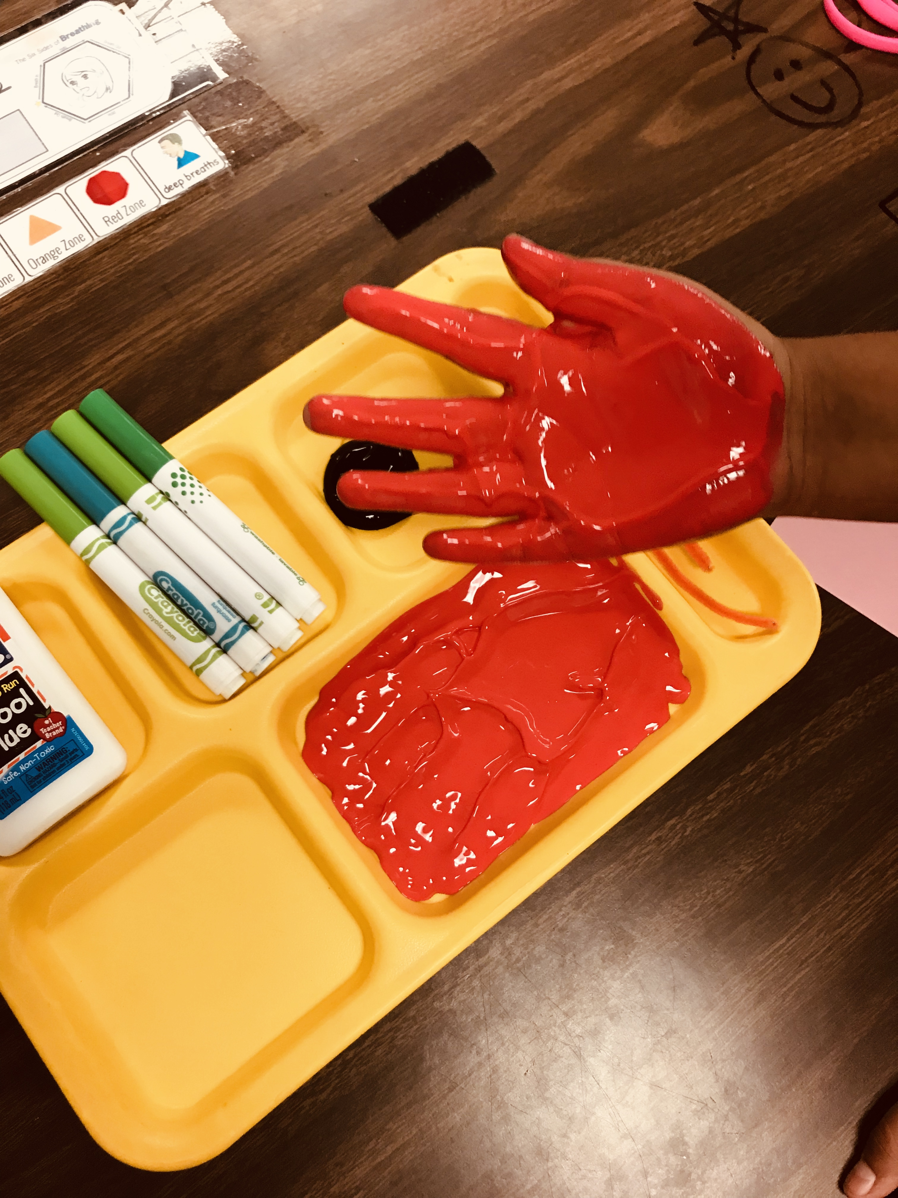 Dipping hand into red paint