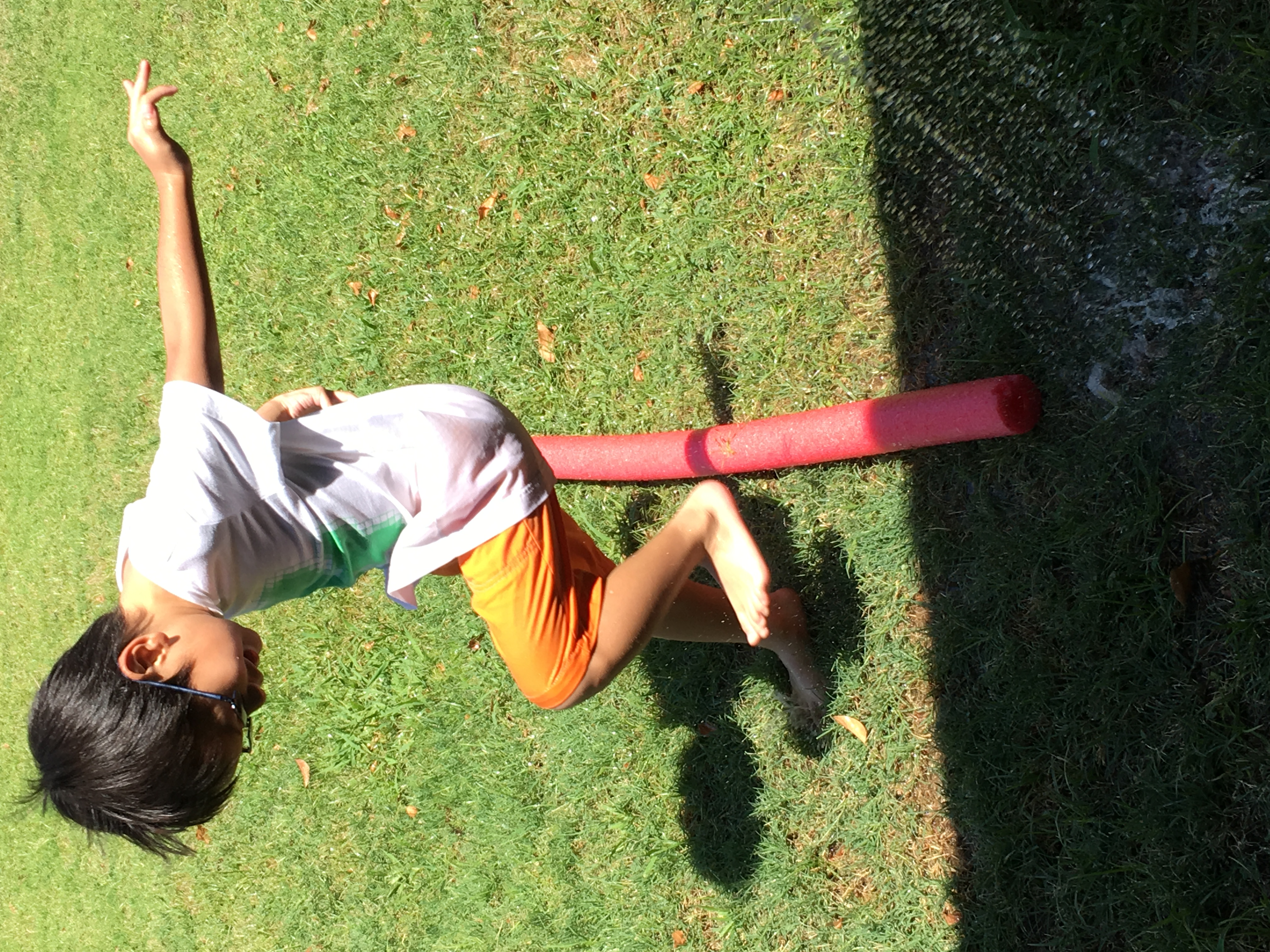 Child hopping over pool noodle