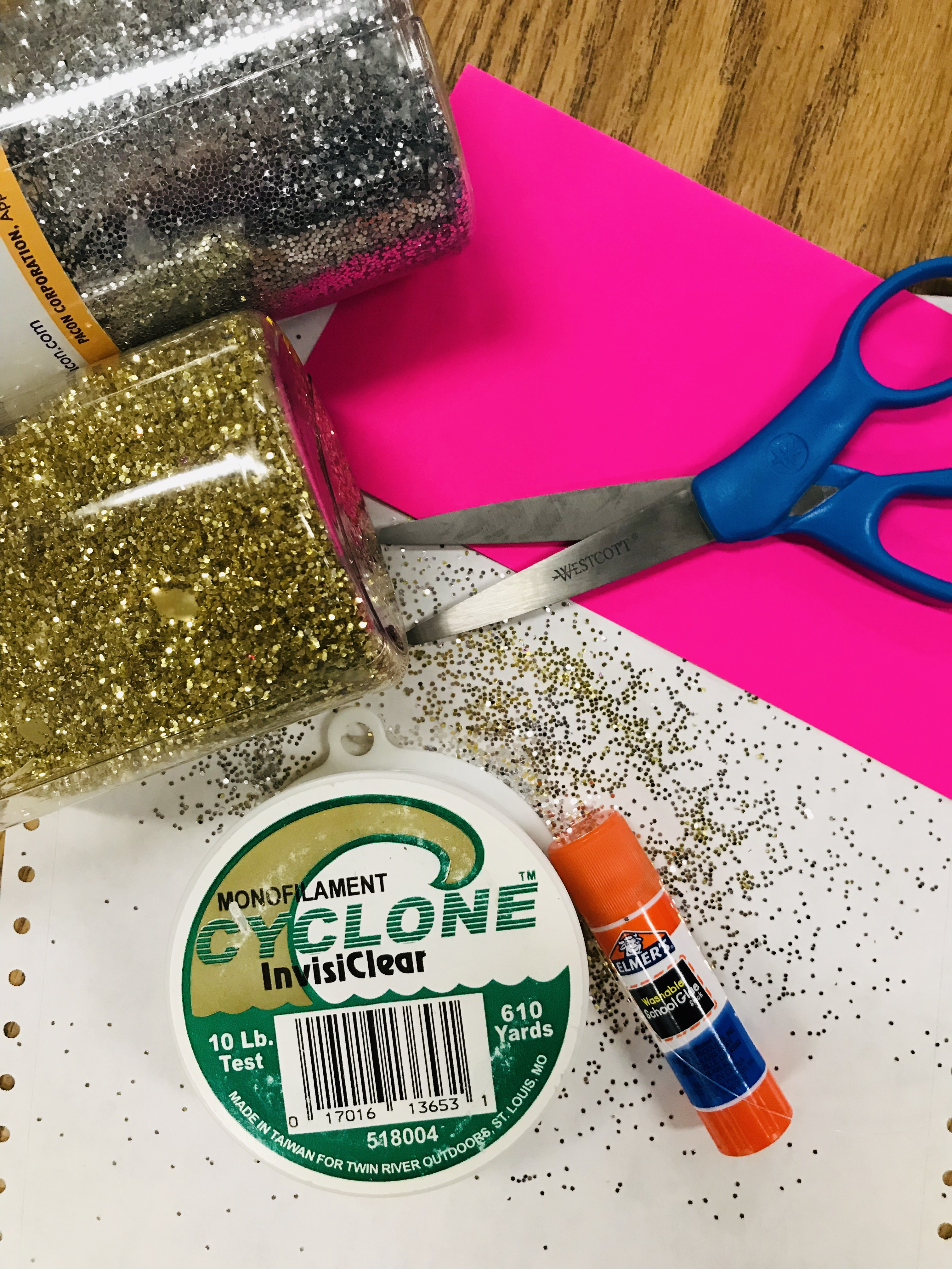 Glue stick, scissors, pink paper and glitter