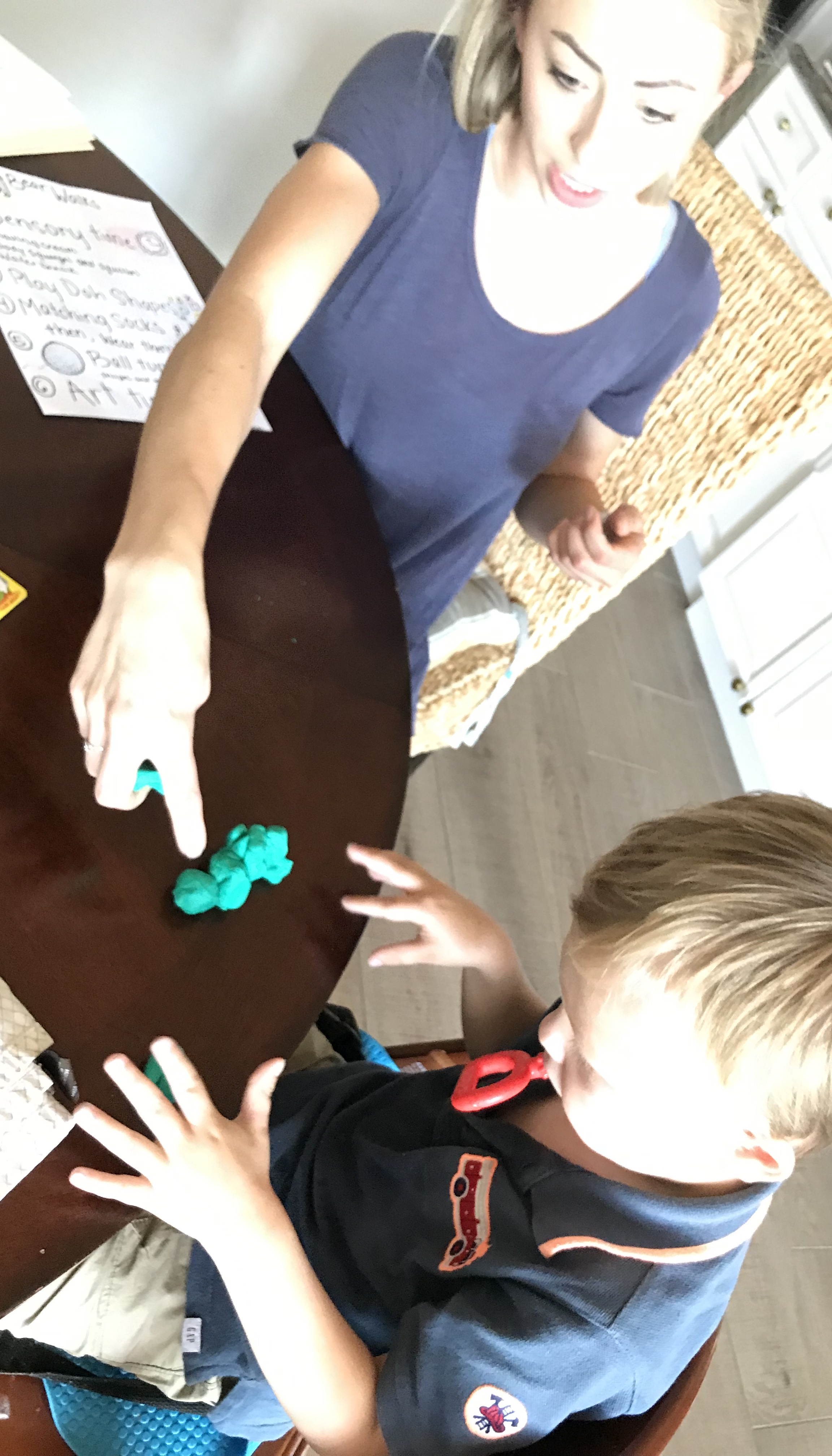 Woman showing young boy green Play Doh