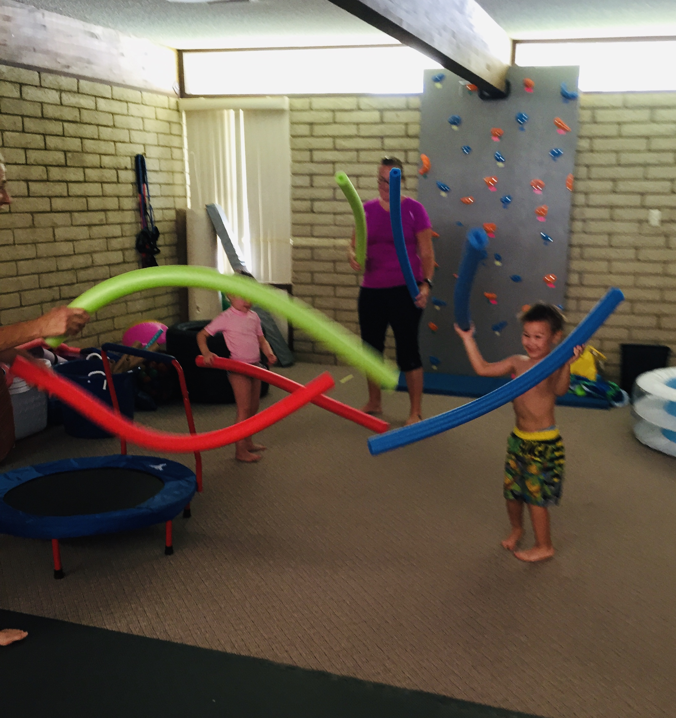 Kids and adult indoors playing with pool noodles