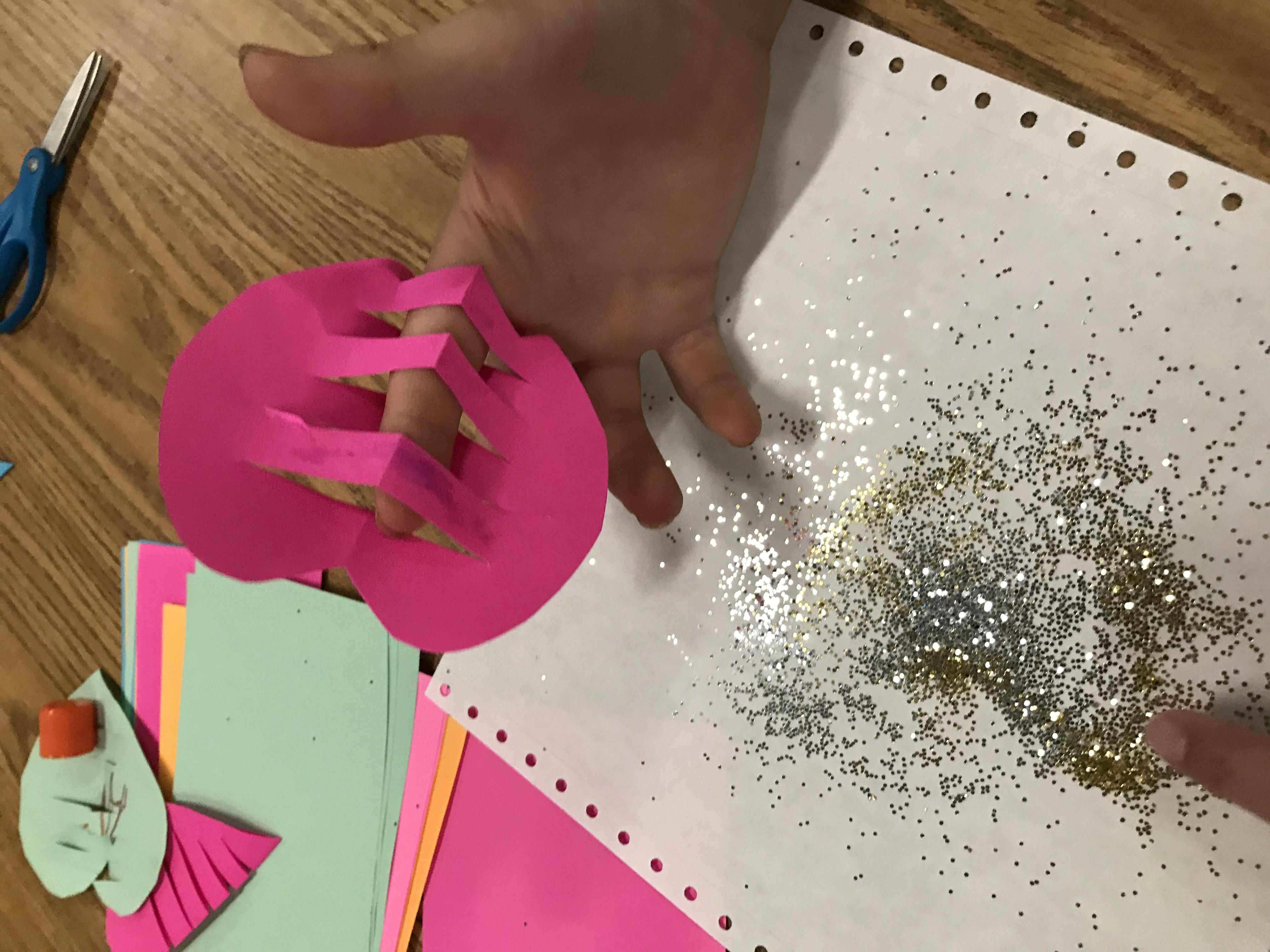 Pushing finger throw slits of paper heart
