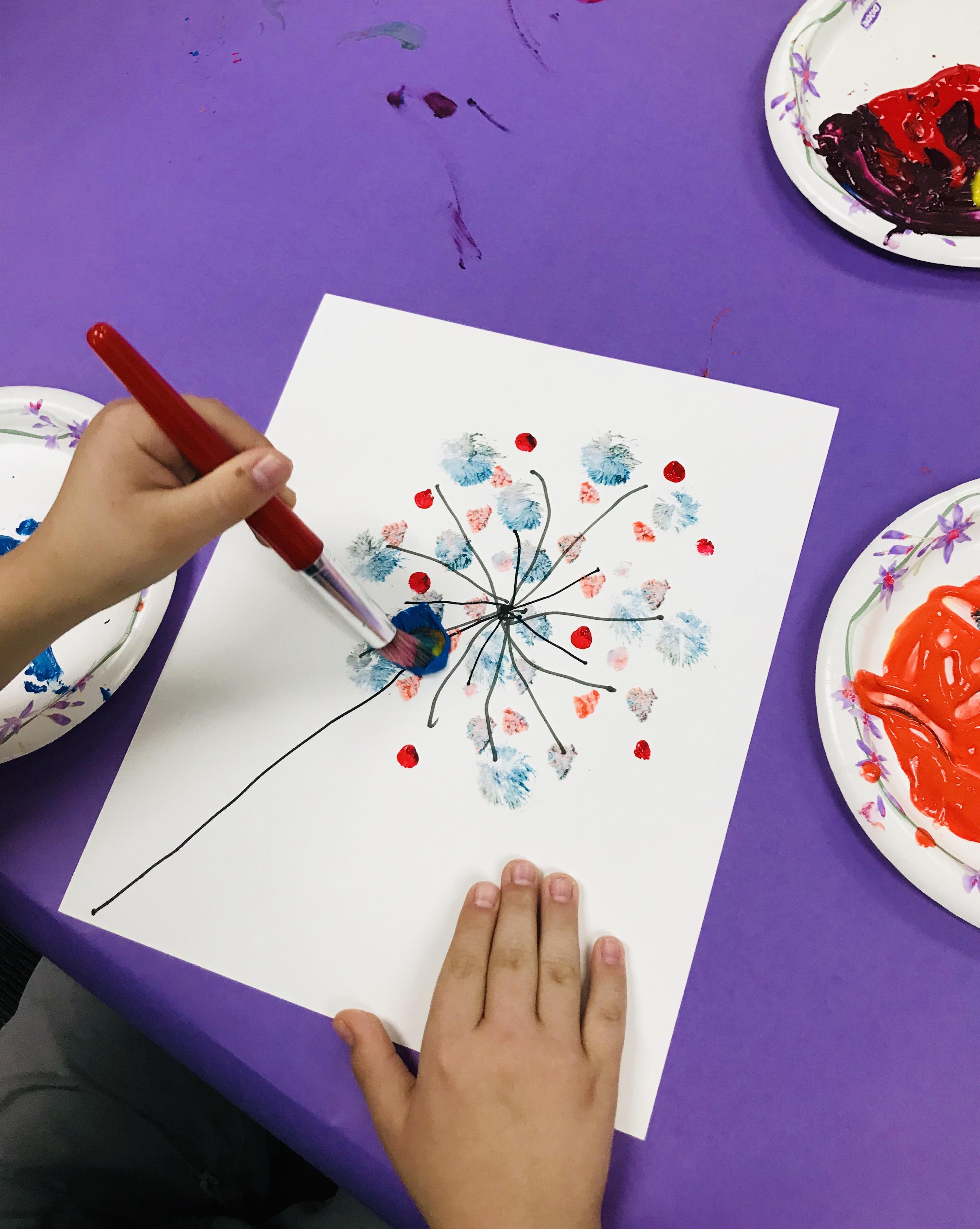 Paint brushing circles on dandelion stem