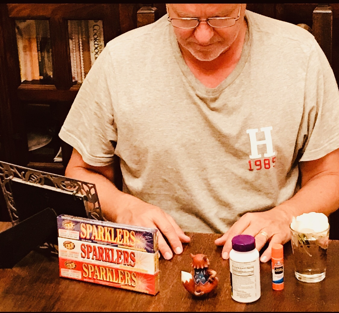Man looking at various items on desk