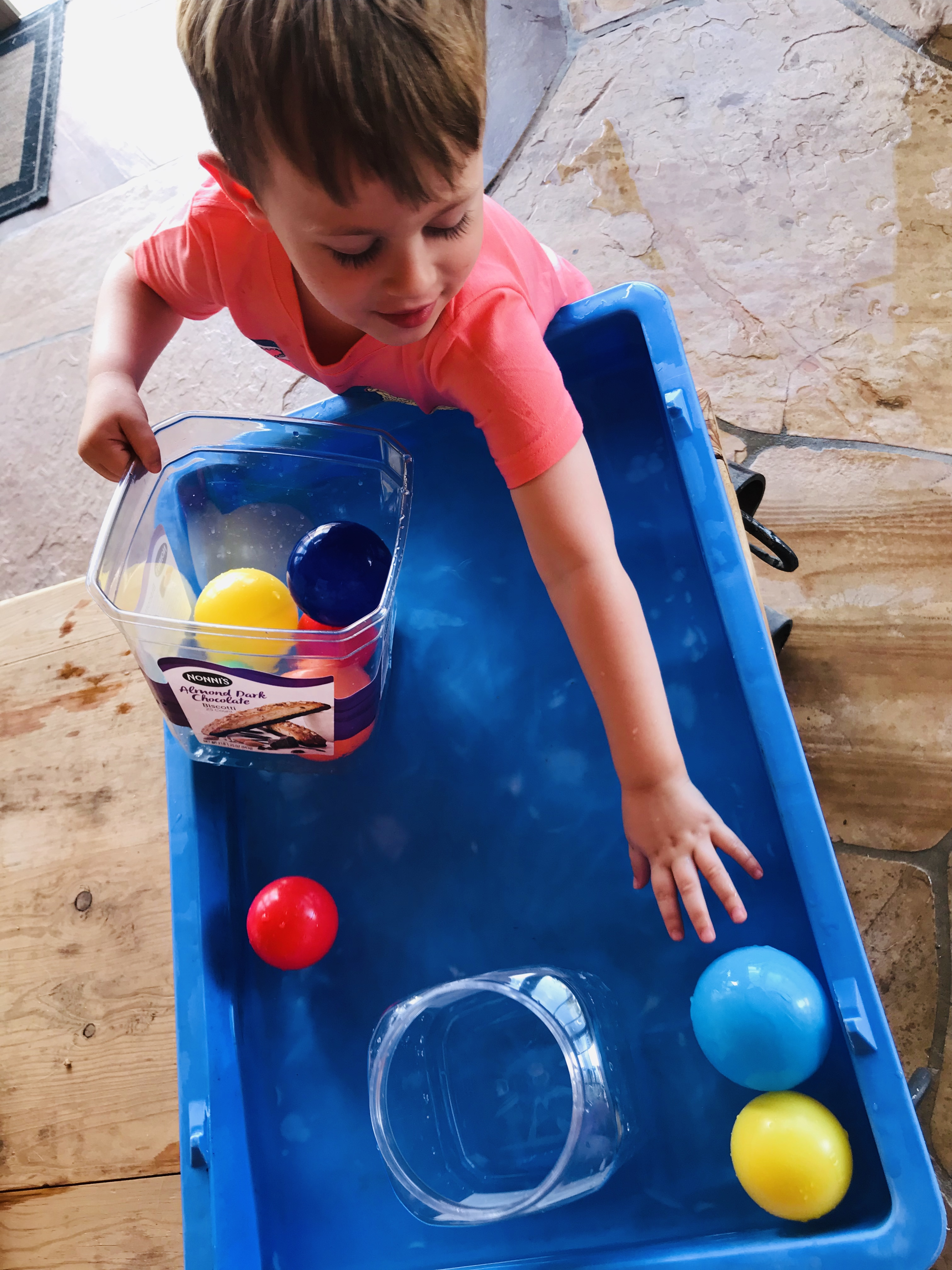 Kid playing with plastic balls in container