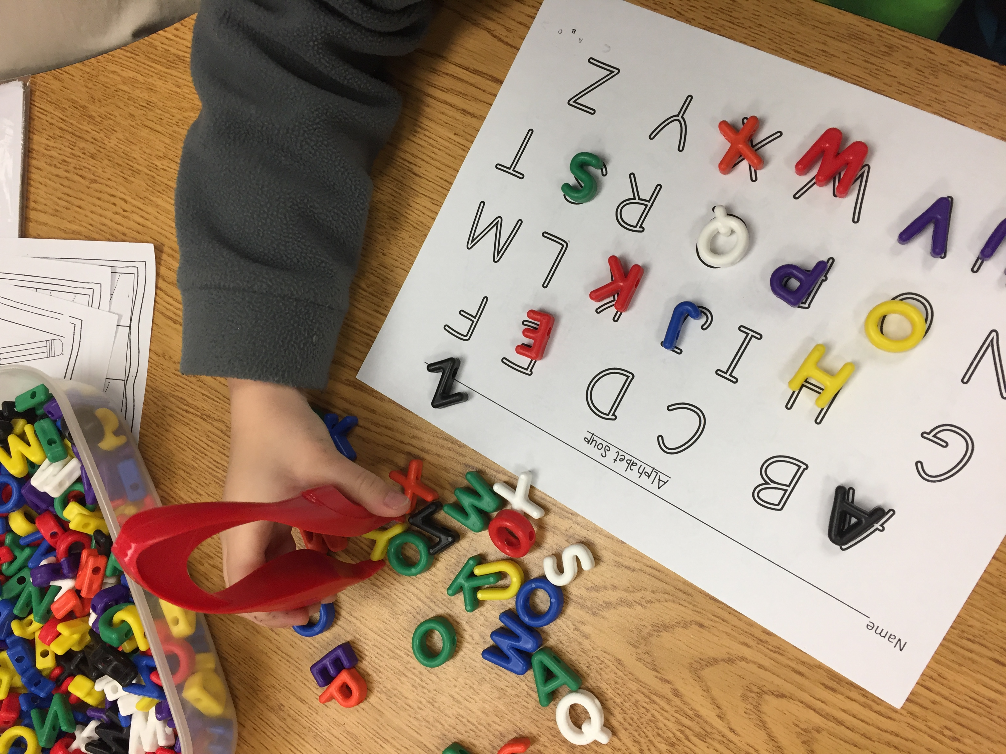 Kid using tongs to pick up letter toys to match on paper