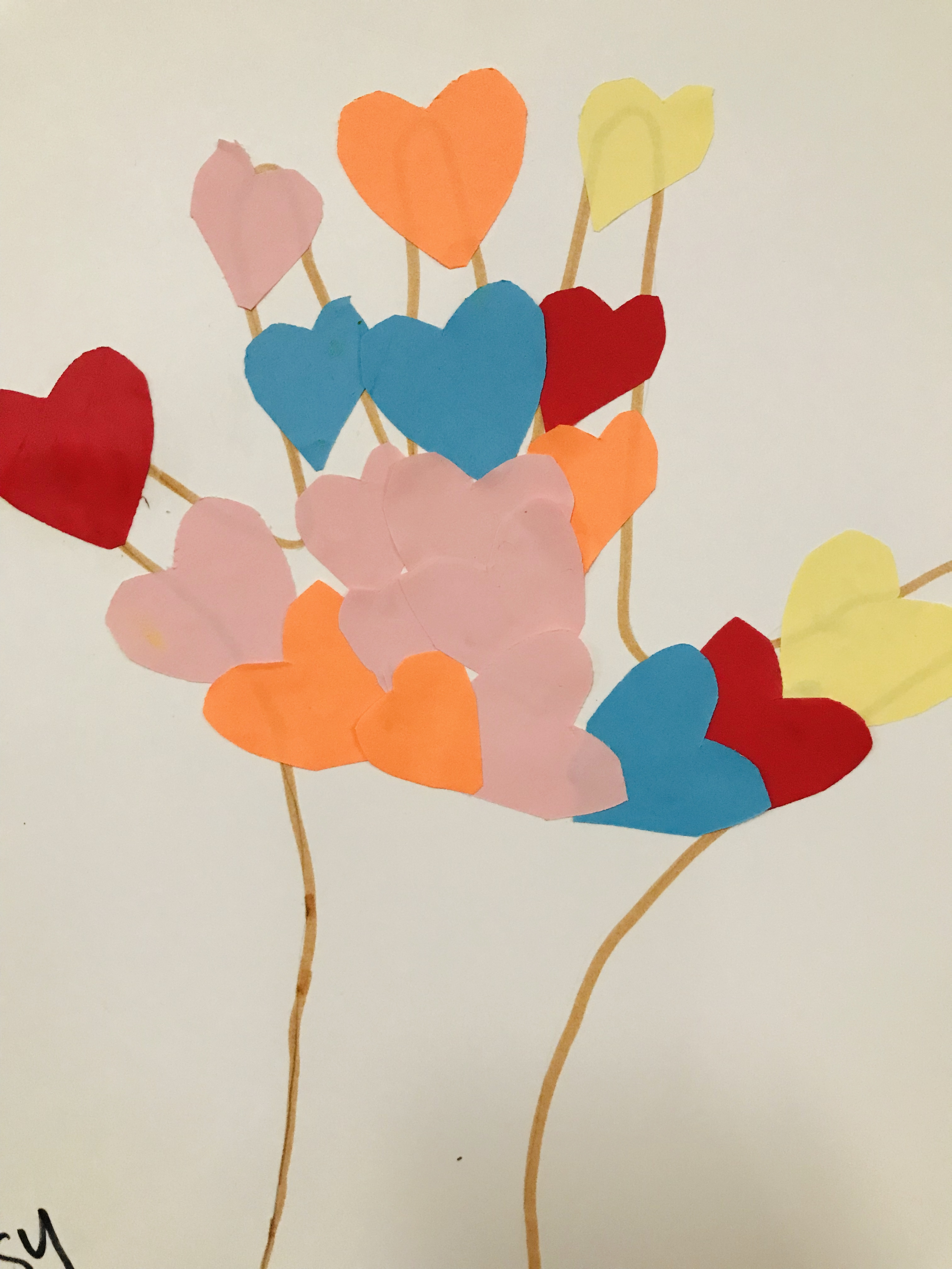 Gluing paper hearts on hand print
