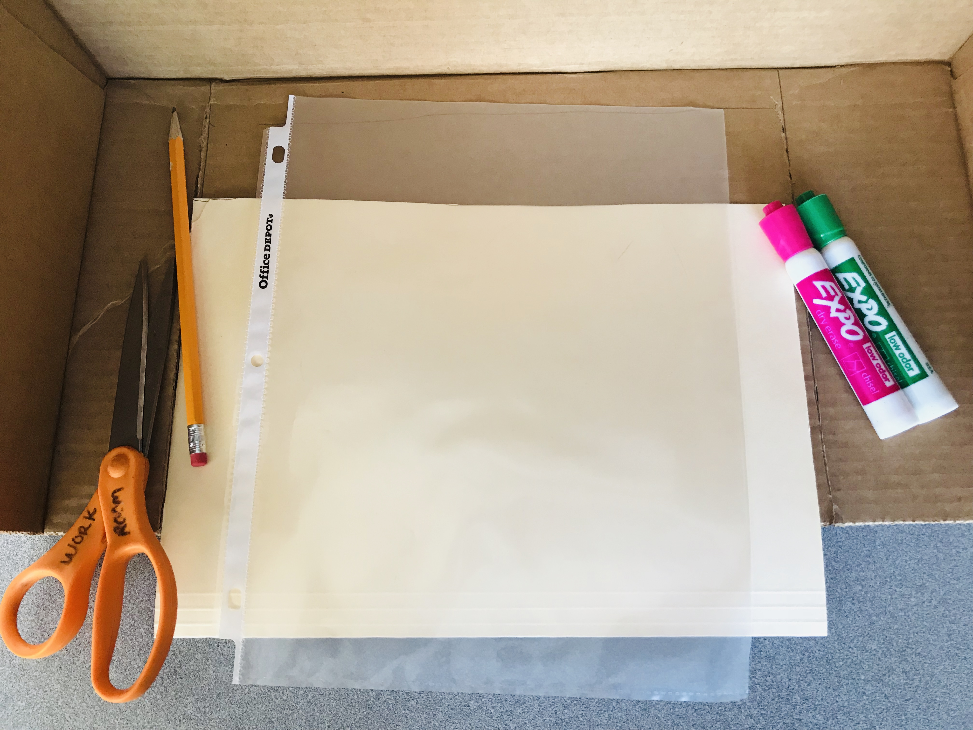 Box with markers, pencil, scissors, folder, and sheet protector