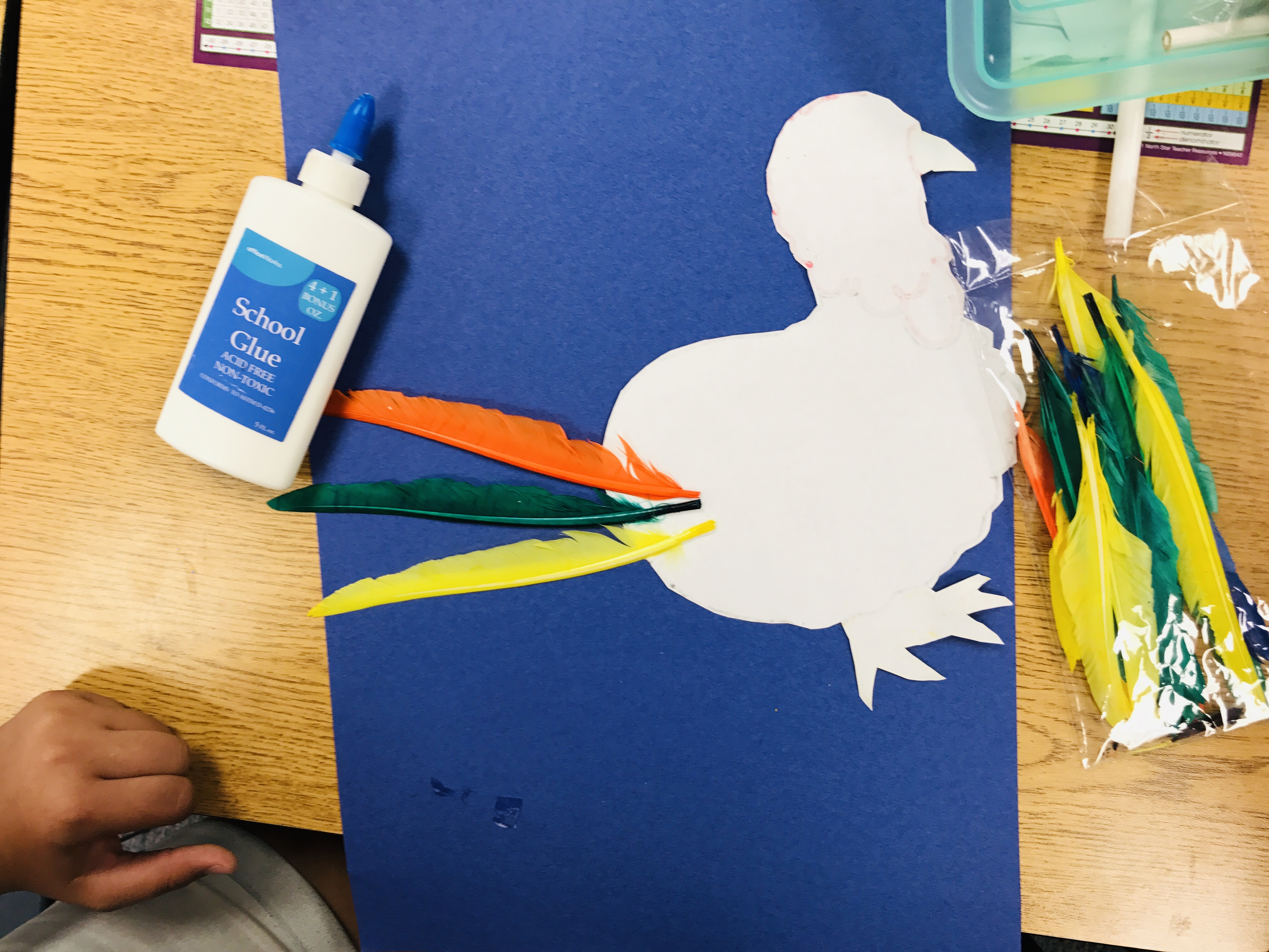 Gluing feathers on paper turkey