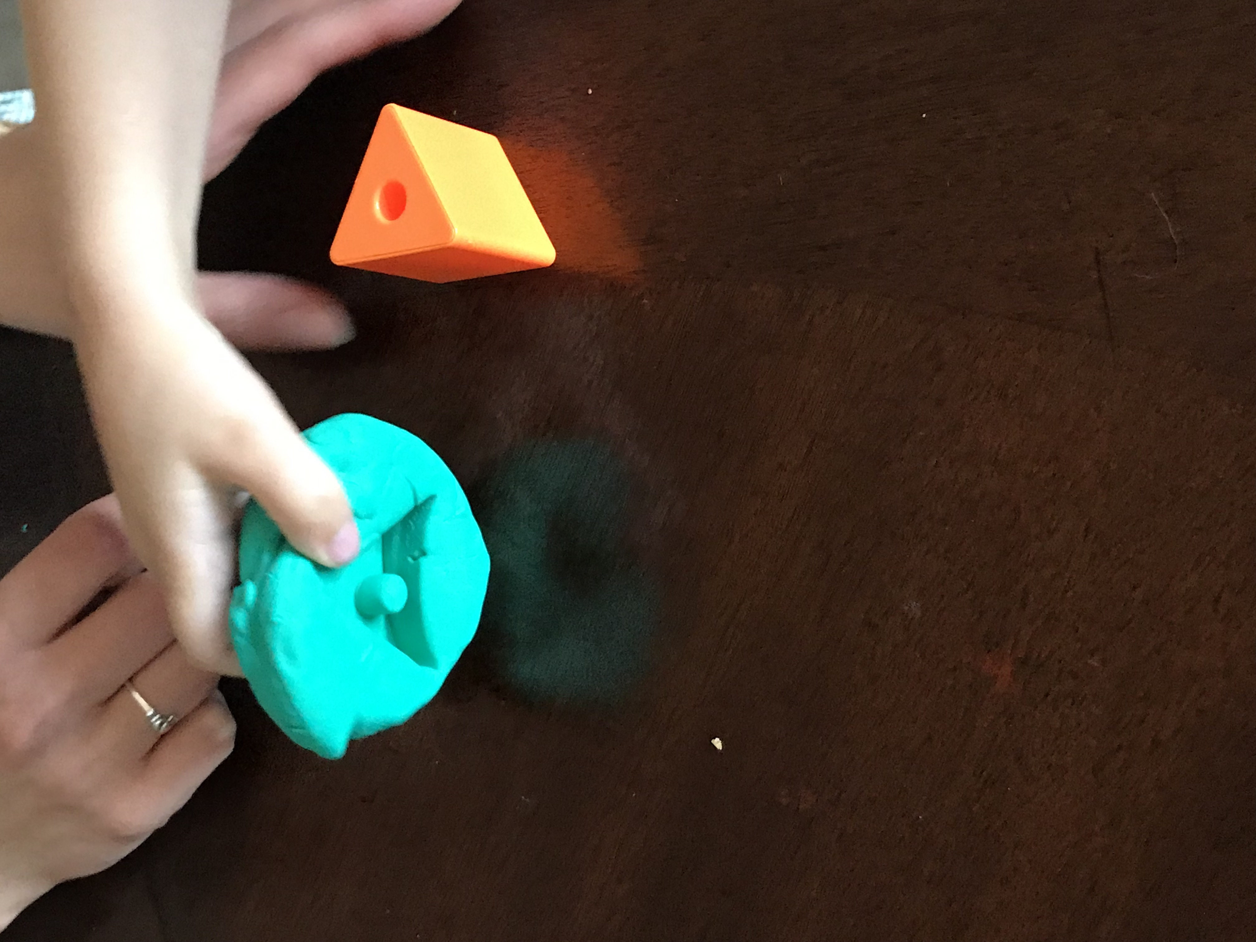 Pressing shape toy into Play Doh