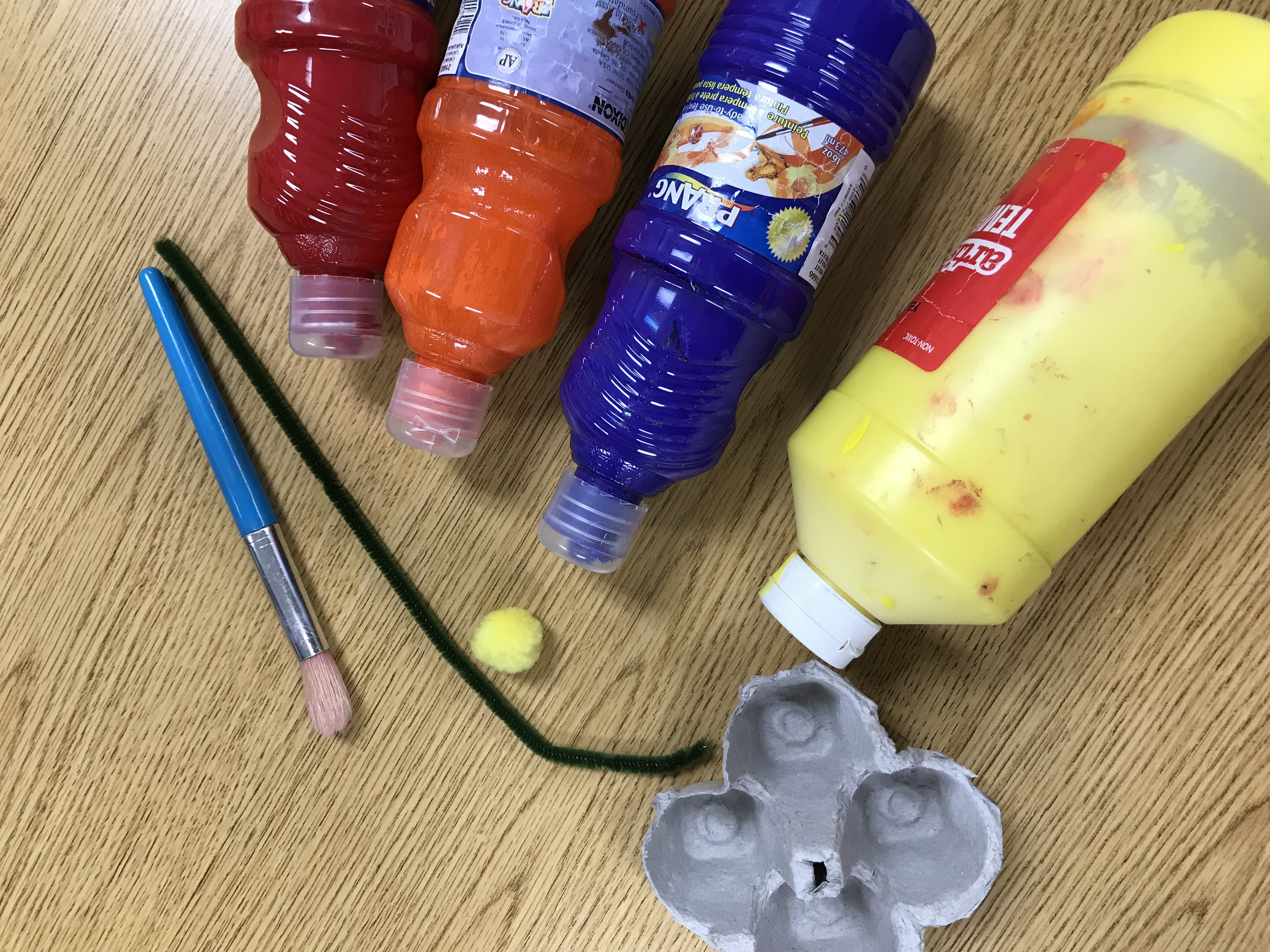 Paints, pipe cleaner stem, paint brush, fuzzy ball and egg carton square