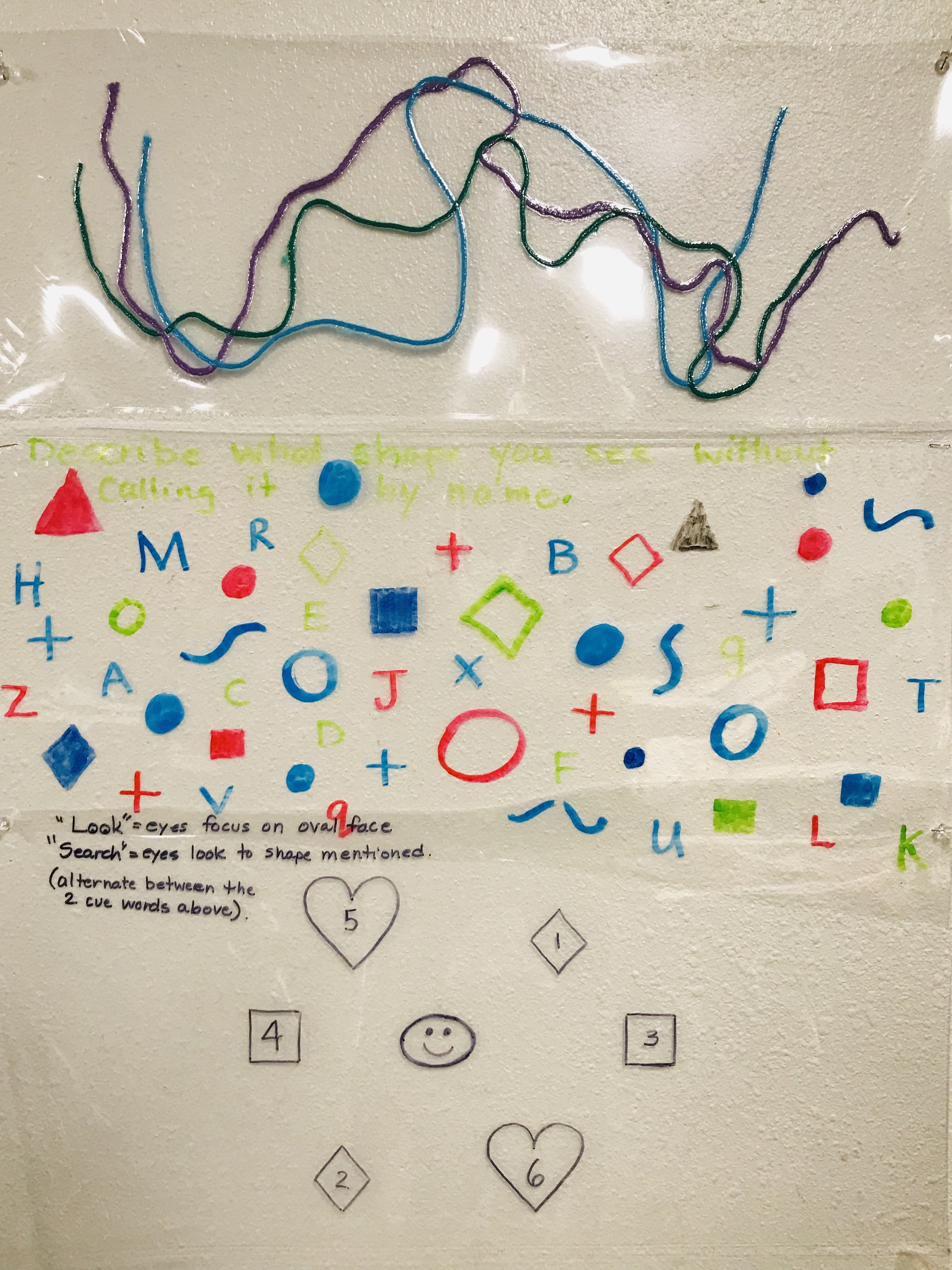 Laminated folder of strings, letters, and shapes