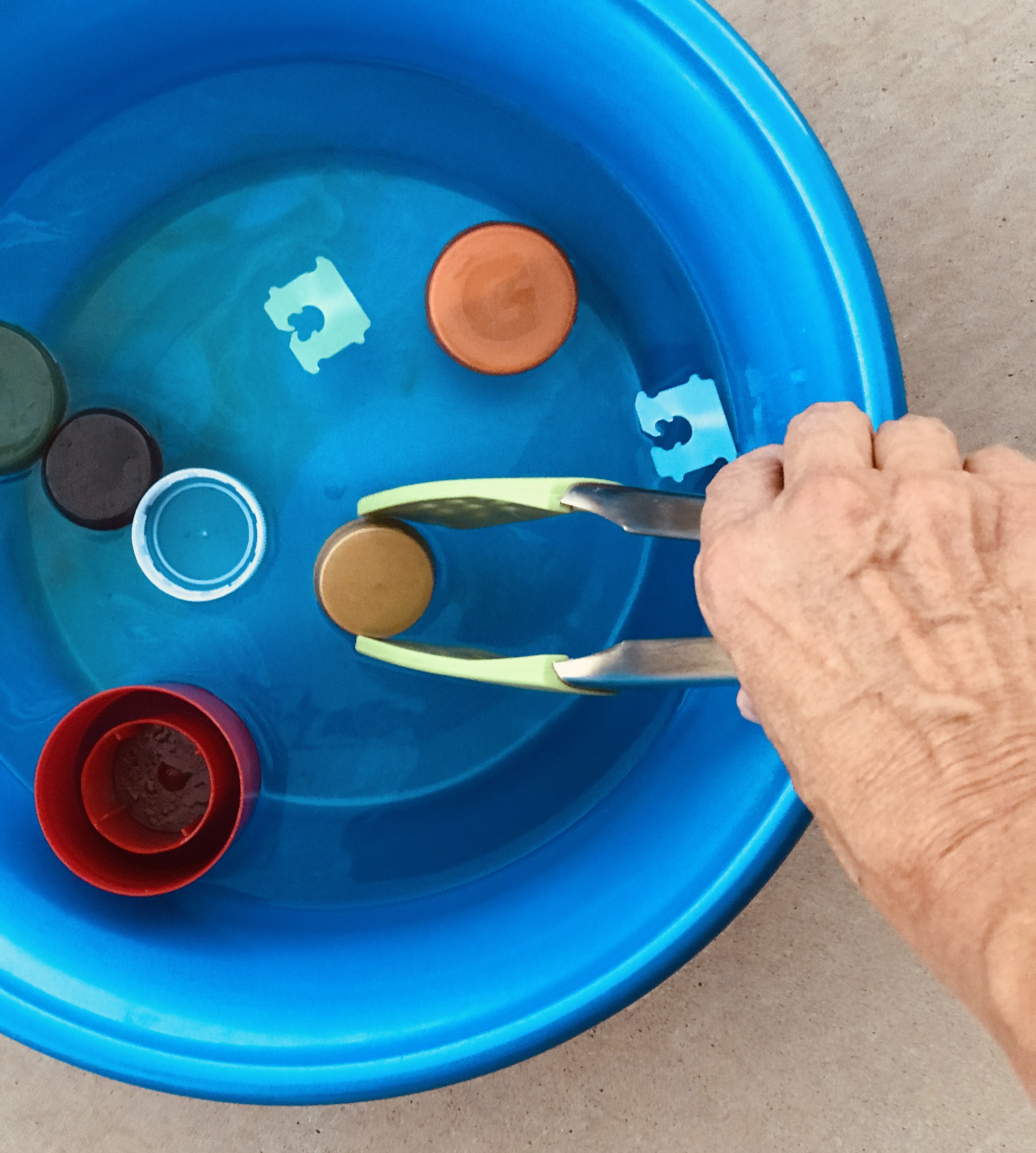 Picking up floating plastic items in water bin with tongs