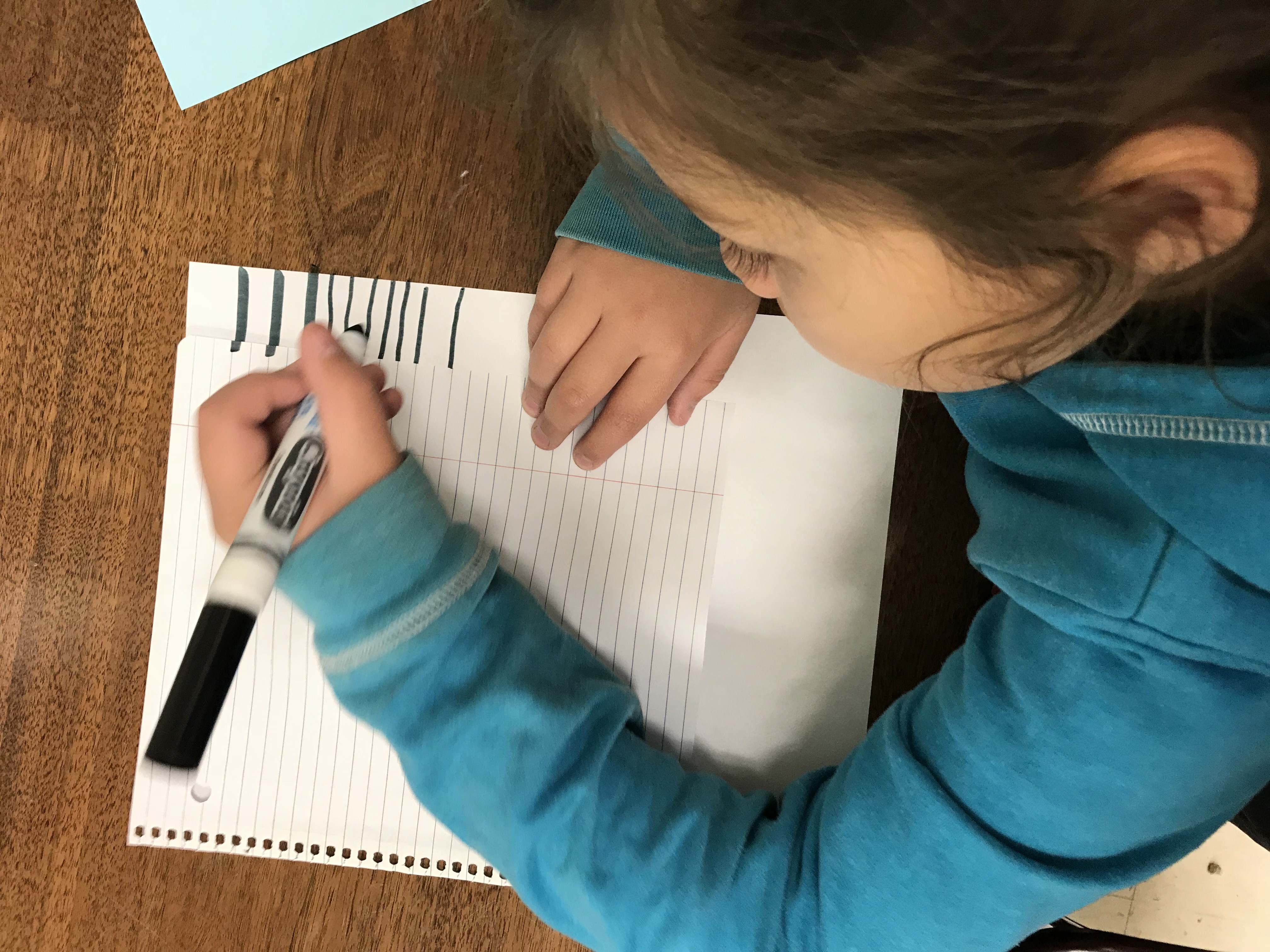 Kid tracing lines from paper