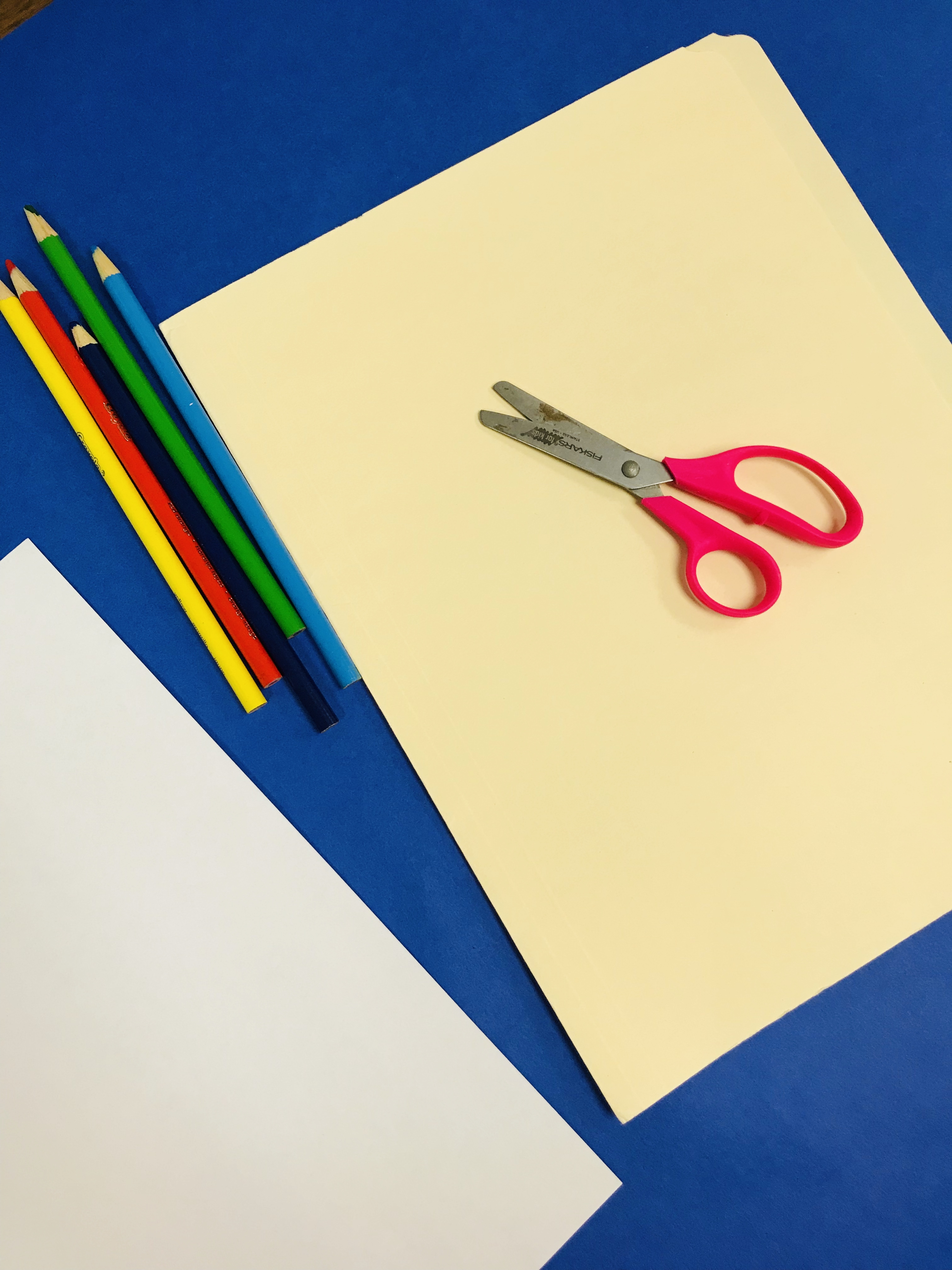 Folder, colored pencils and scissors