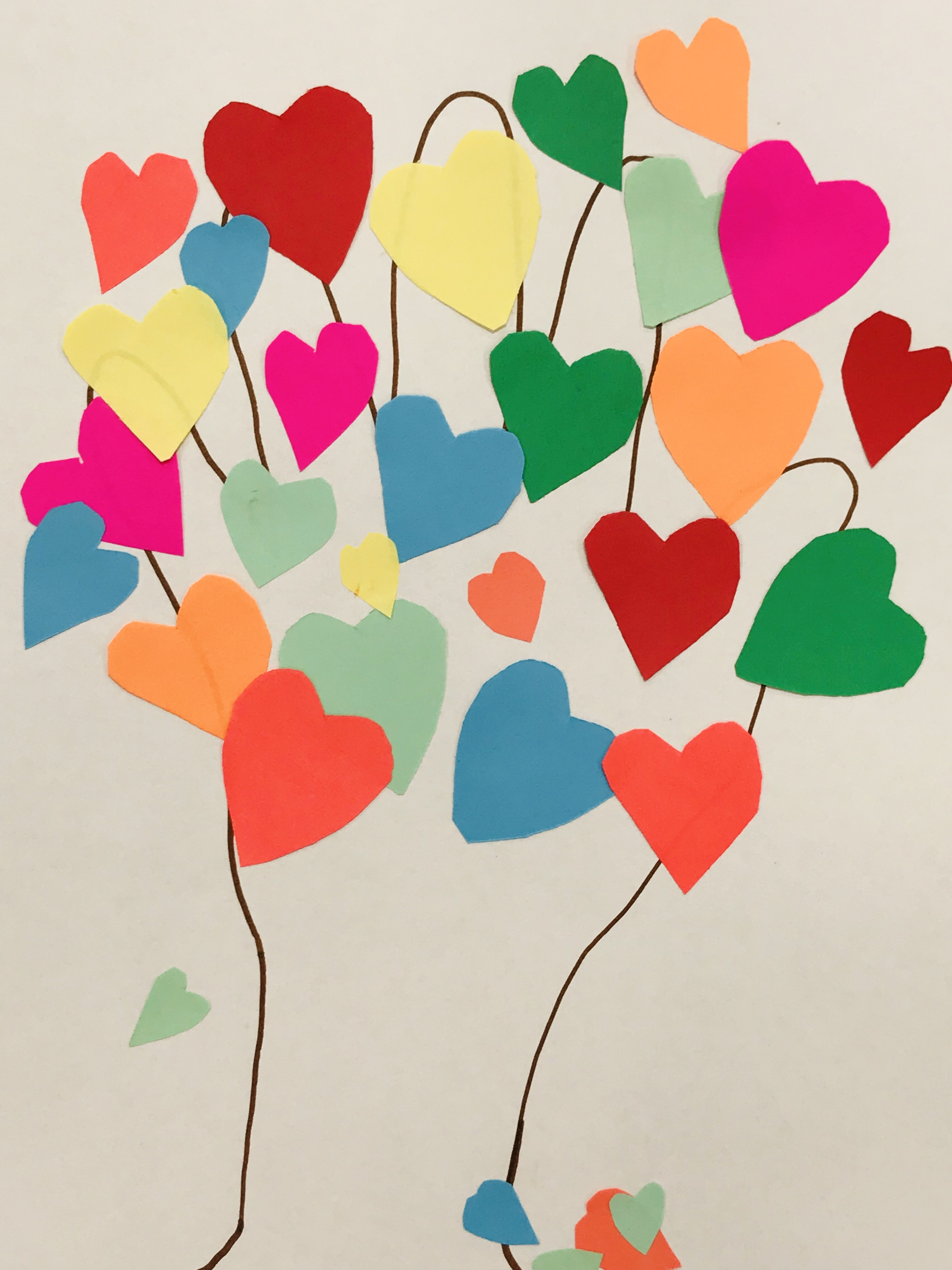Glued paper hearts on hand print
