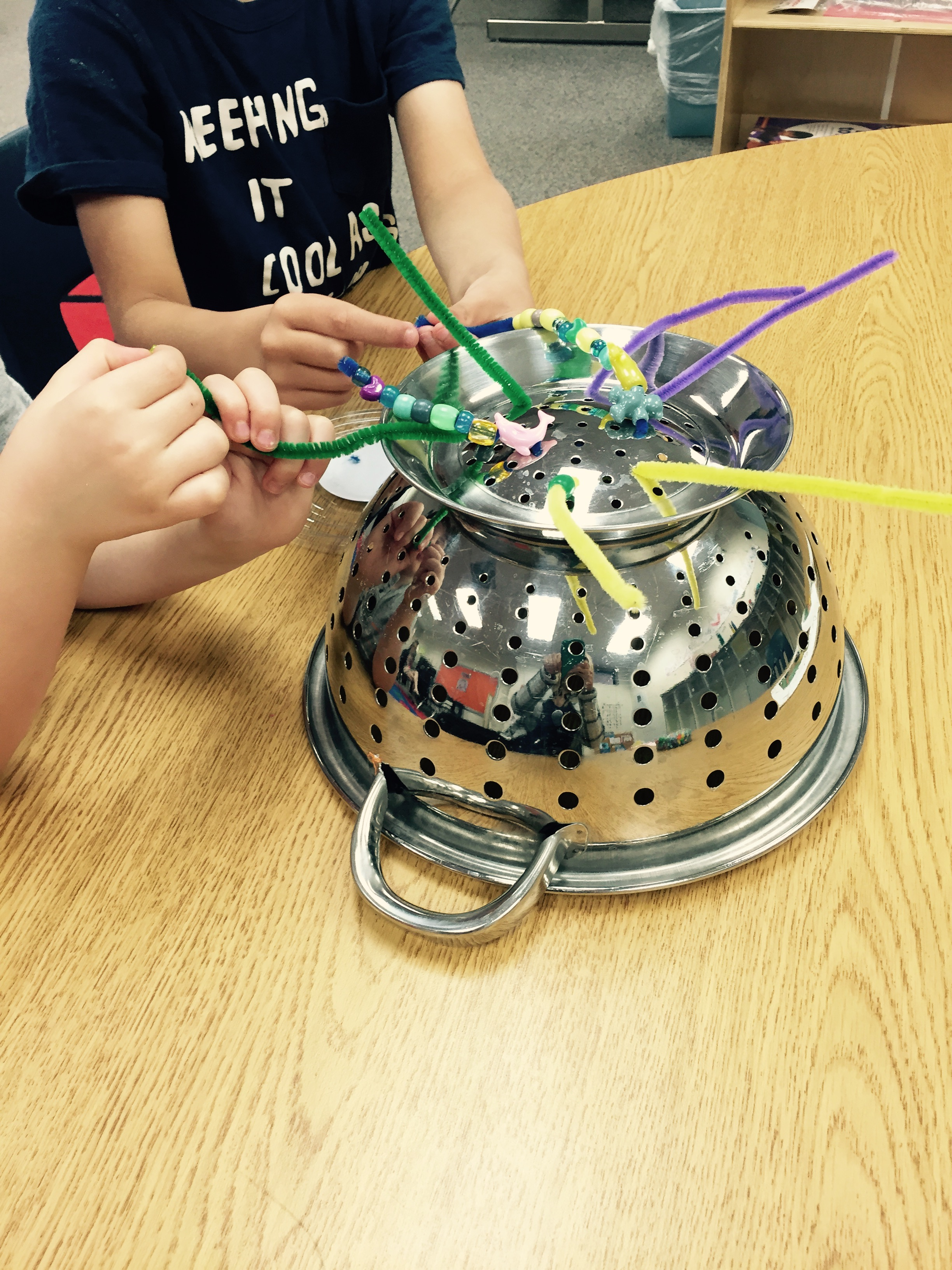 Pulling pipe cleaner strings from colander