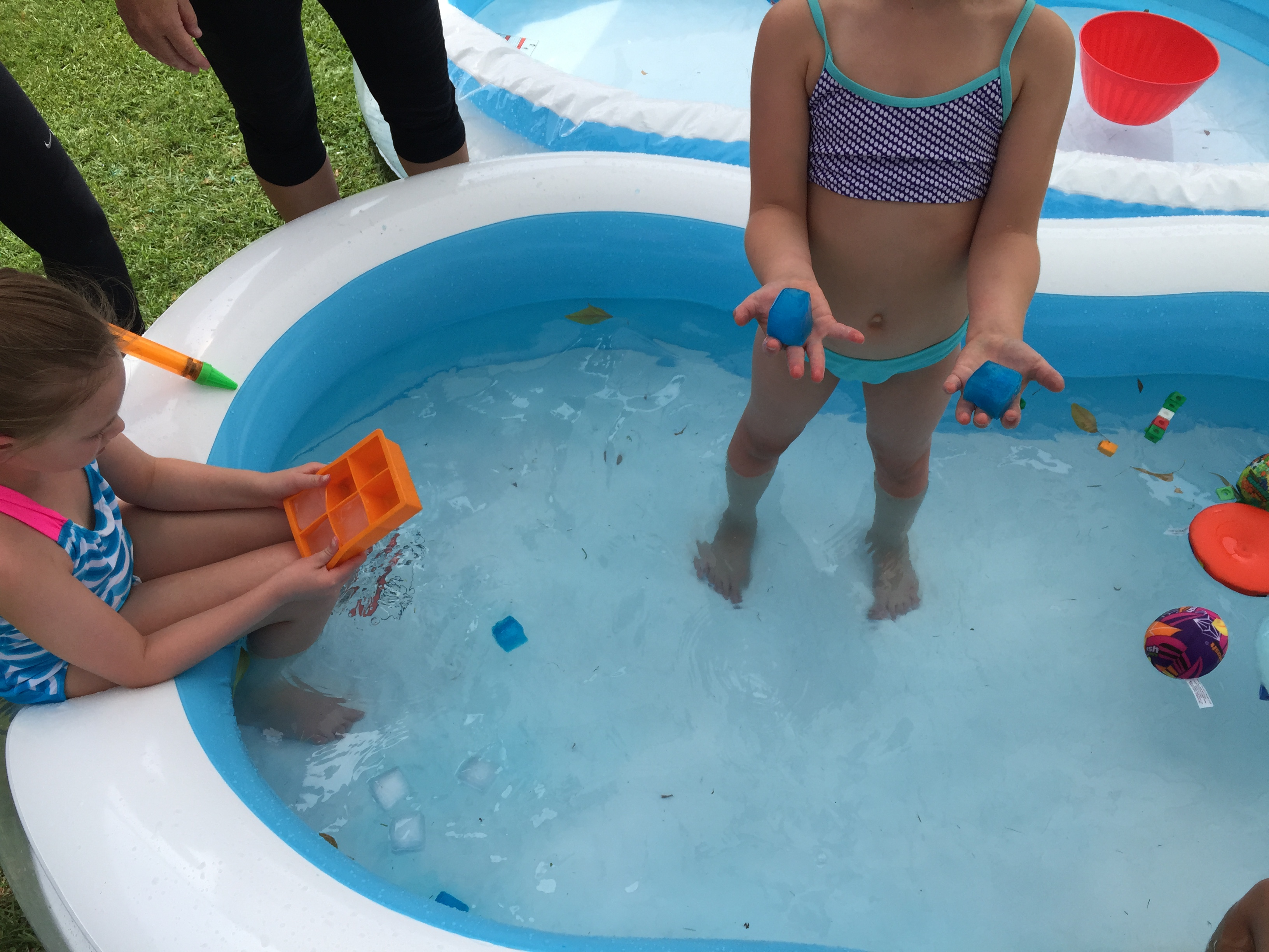 Kids playing with toys floating in kiddie pool